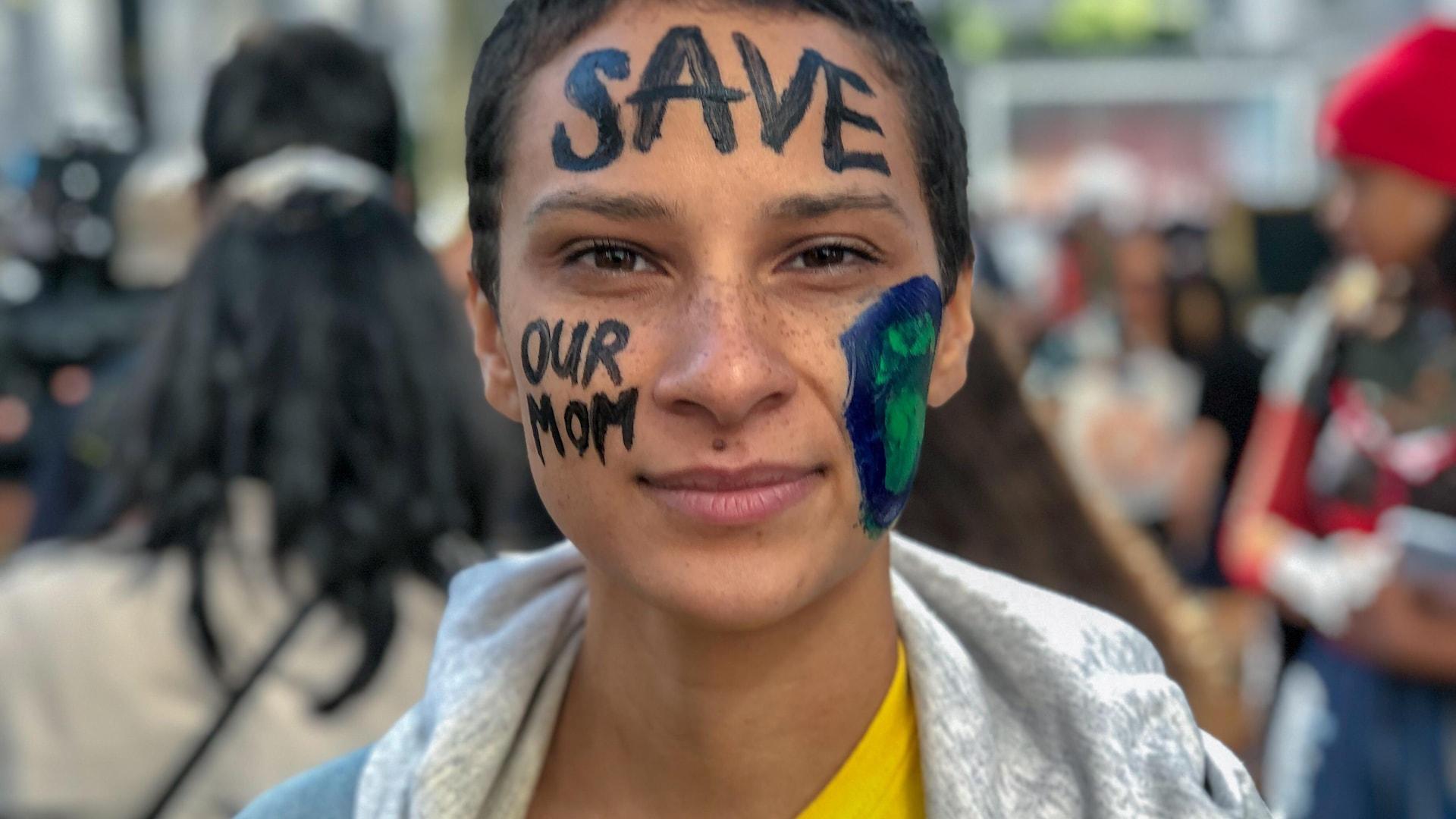 Un manifestant dont le visage a été peint et sur lequel il est écrit «sauvez notre mère».