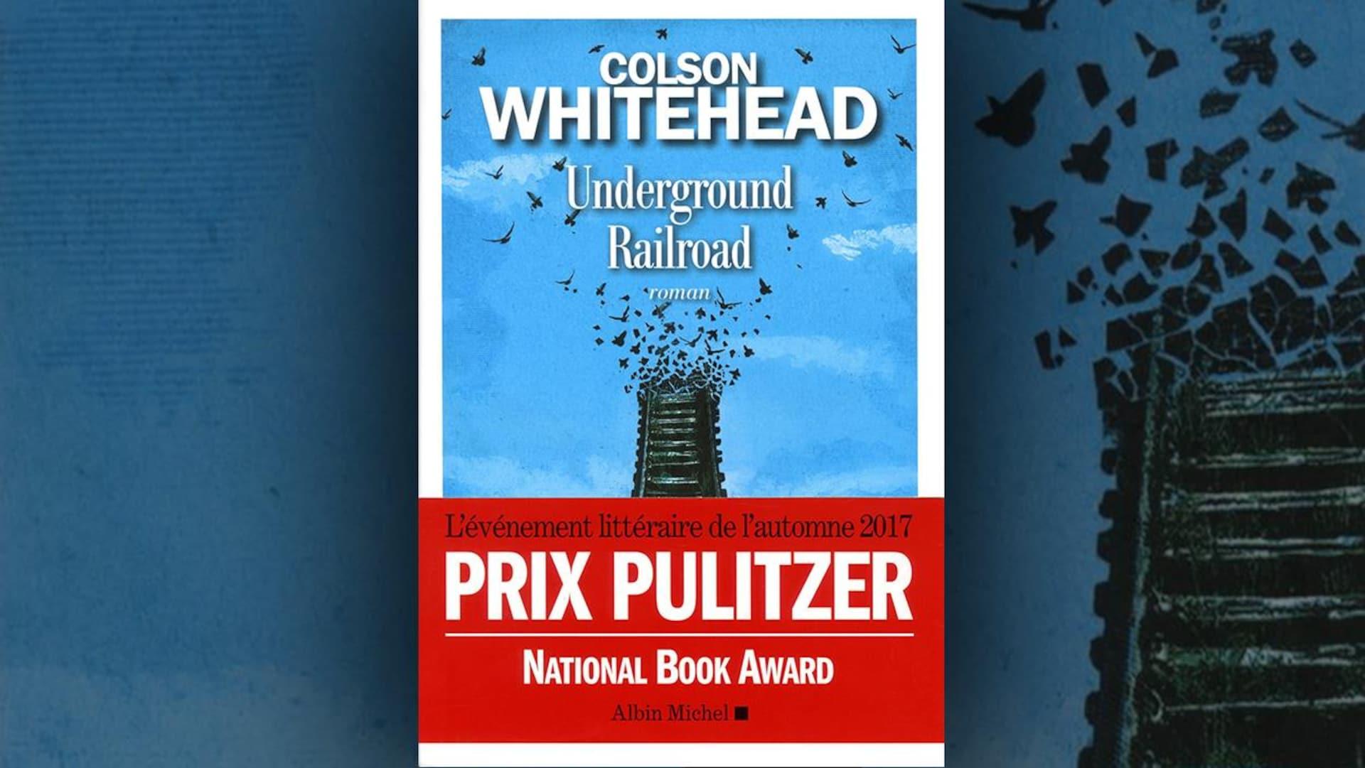 La couverture du livre  Underground Railroad  de Colson Whithehead : illustration de rails de chemin de fer qui volent en éclats et se transforment en oiseaux sur fond de ciel bleu. Un bandeau rouge précise que le livre est «L'événement littéraire de l'automne 2017» et qu'il a gagné le Prix Pulitzer et le National Book Award.