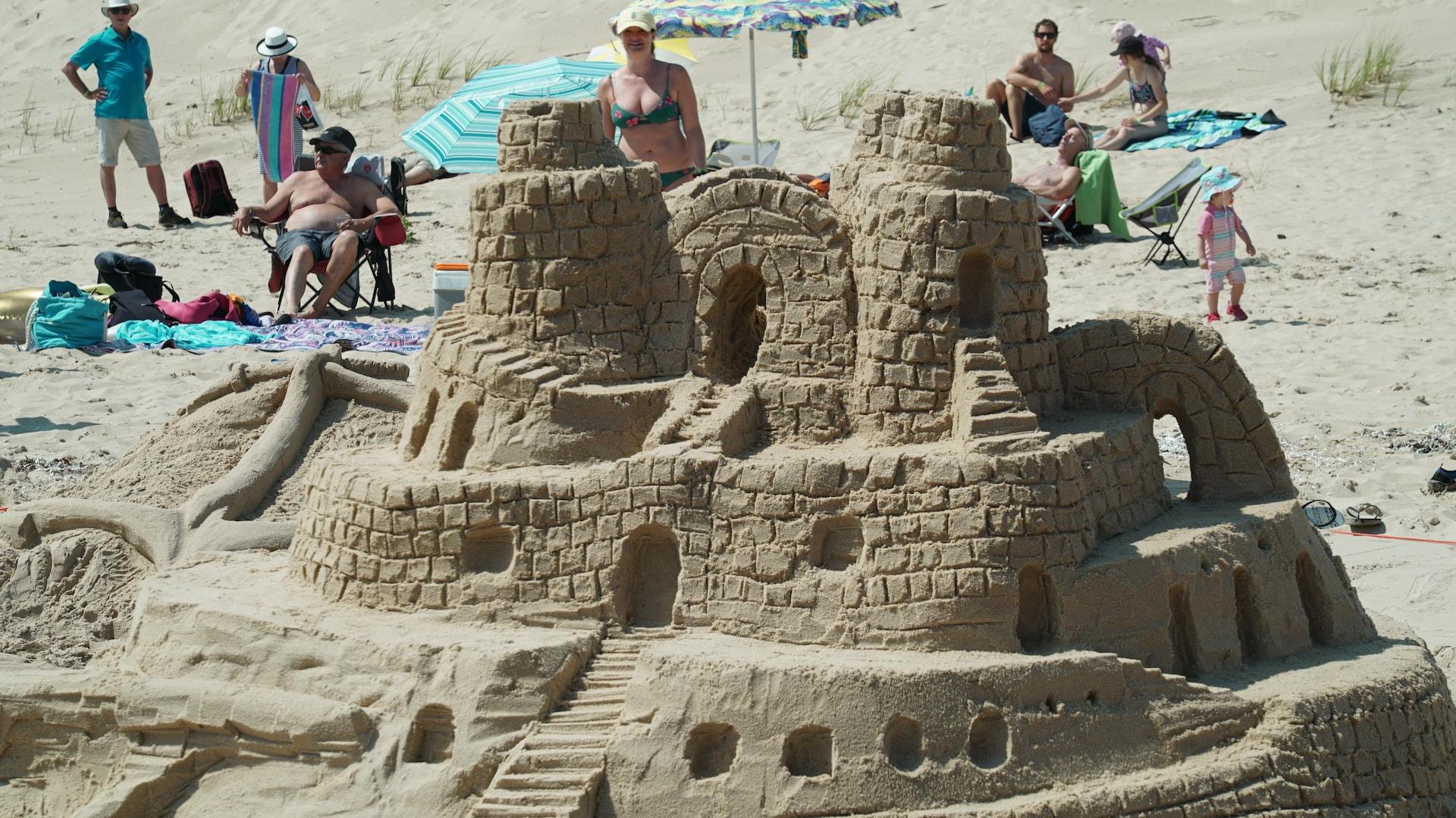 Gros plan sur un château de sable avec plusieurs paliers et de petits creux en guise de fenêtres.
