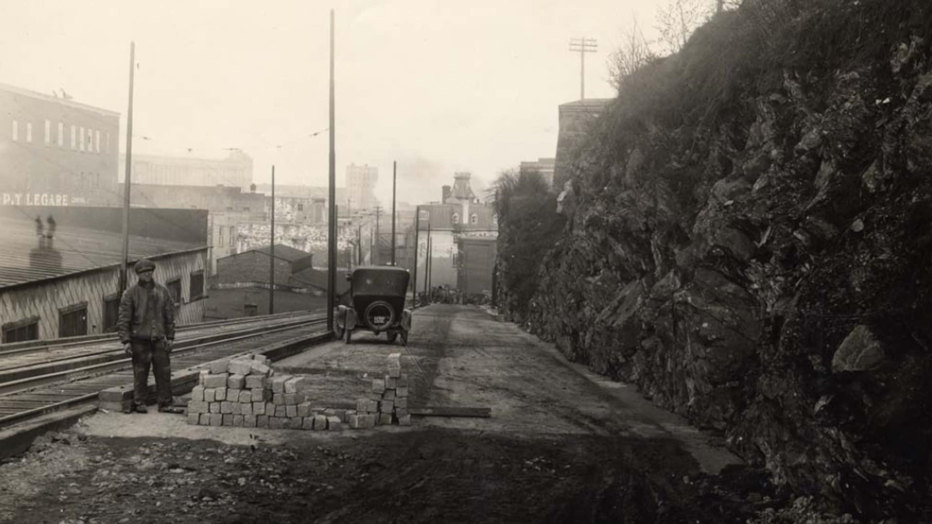 Un ouvrier nous regarde alors que des pavés s'empilent devant lui sur une photo des années 1920. Une voiture est stationnée un peu plus bas. Les travaux permettent de créer un passage pour les voitures le long de la falaise.