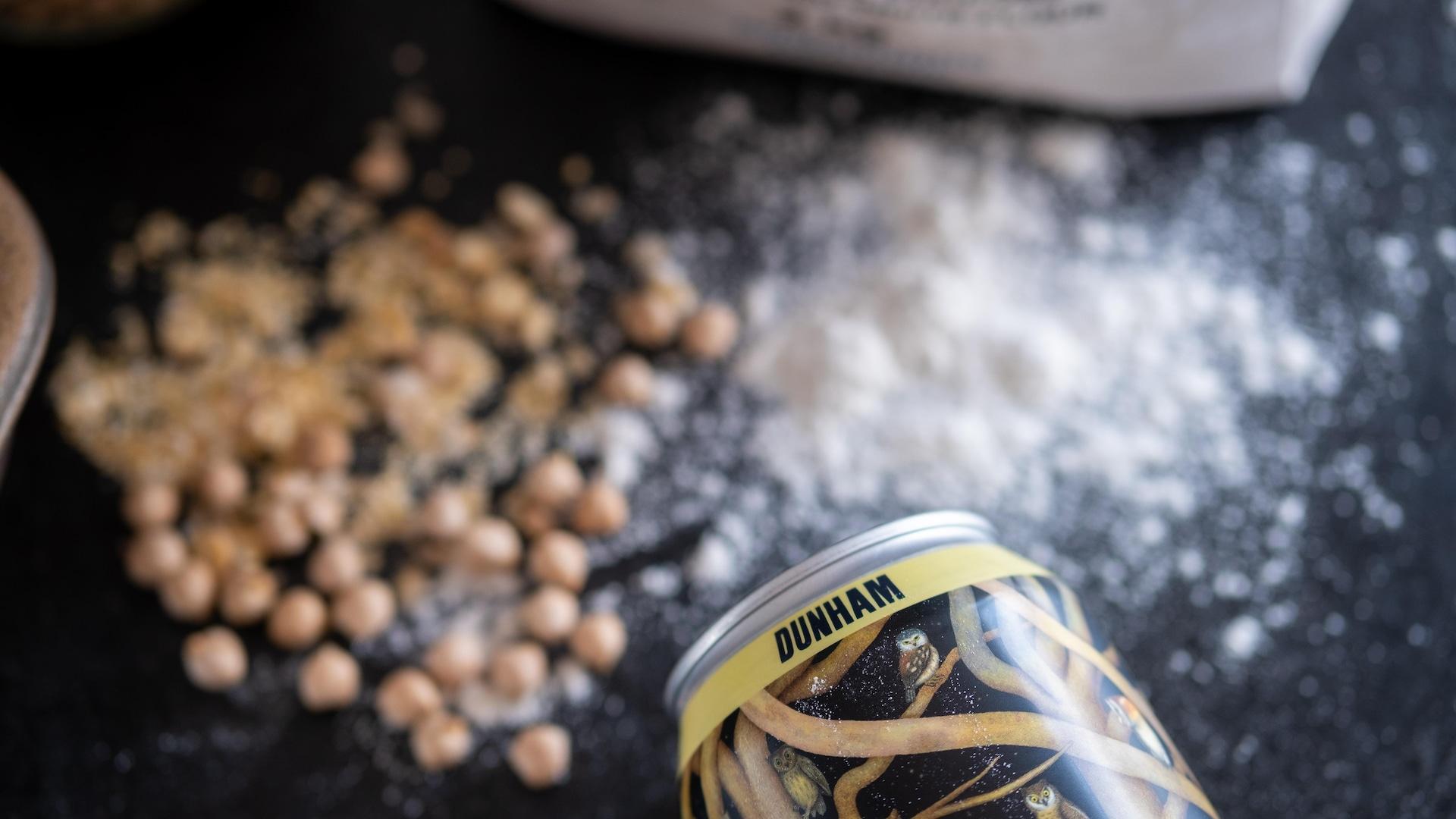 Une cannette de bière en avant-plan, des grains et de la farine sur la table en arrière-plan.