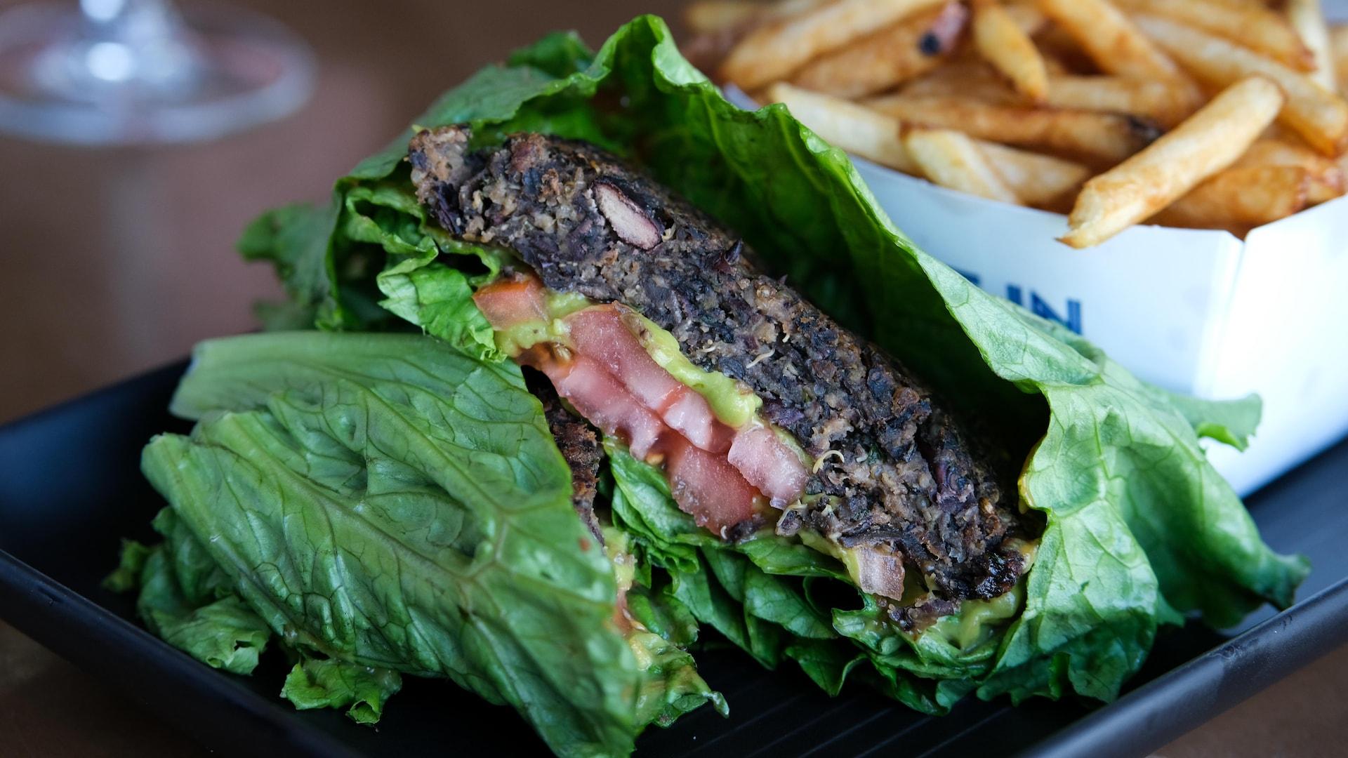 Le burger végétalien est présenté entre deux feuilles de laitues et garni de tomates et d'une purée d'avocat.