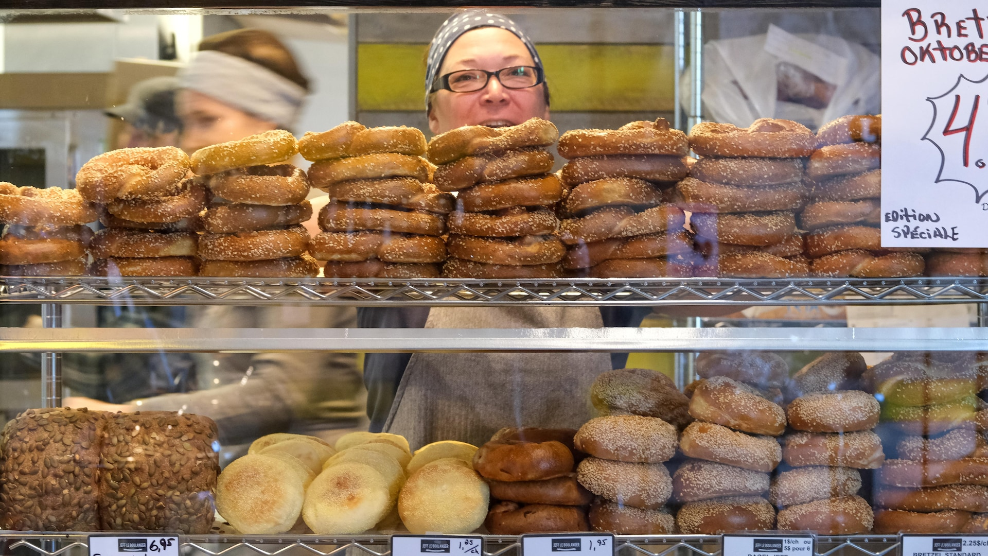 Des bretzels, muffins anglais, et pains dans un présentoir de boulangerie.