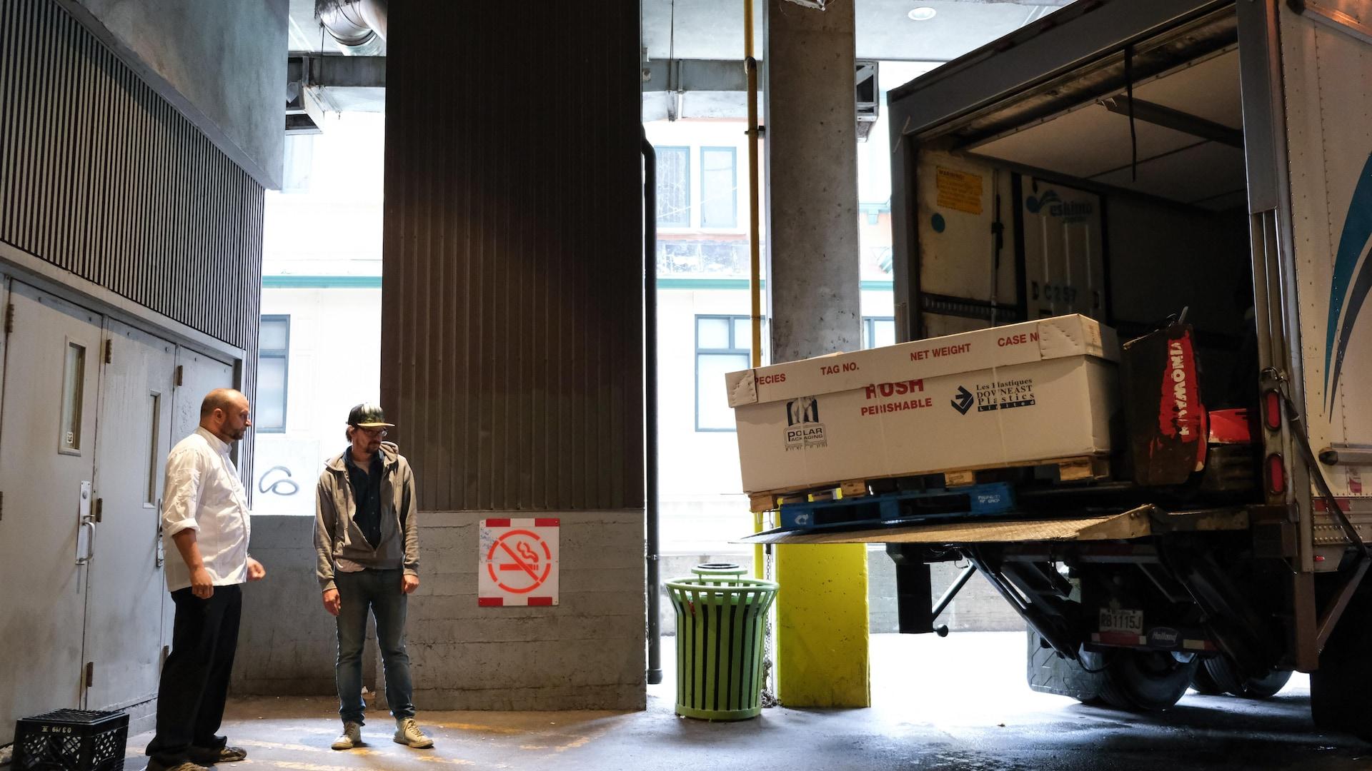 Deux hommes dans un entrepôt attendent un camion de livraison