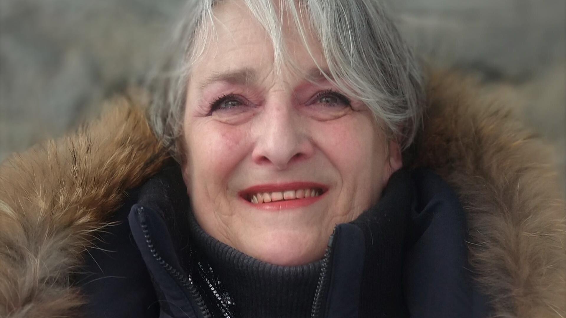 Portrait en couleur, en extérieur, d'une femme aux cheveux gris portant un manteau noir avec une bordure de fourrure. Elle regarde au loin, face à l'appareil photo, et sourit.