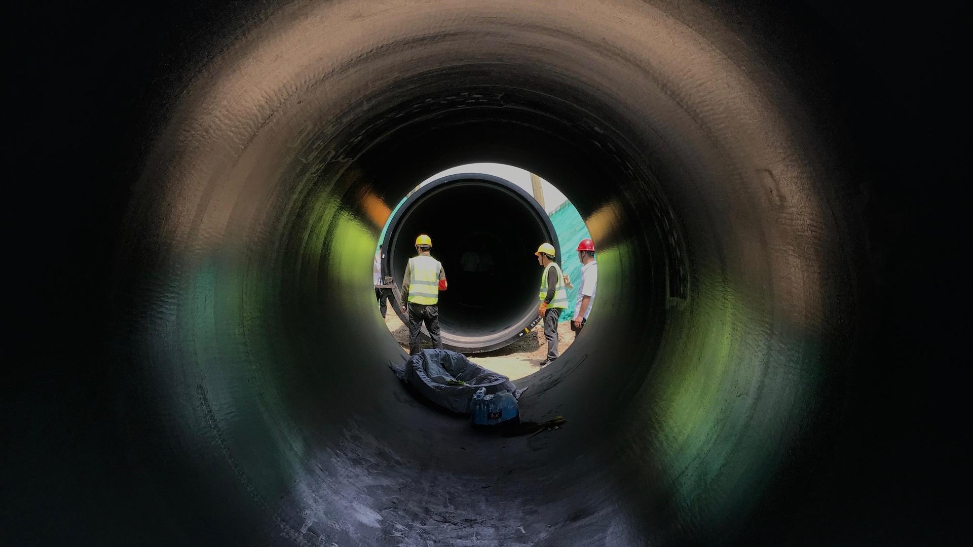On voit trois travailleurs au travers un pipeline vide.