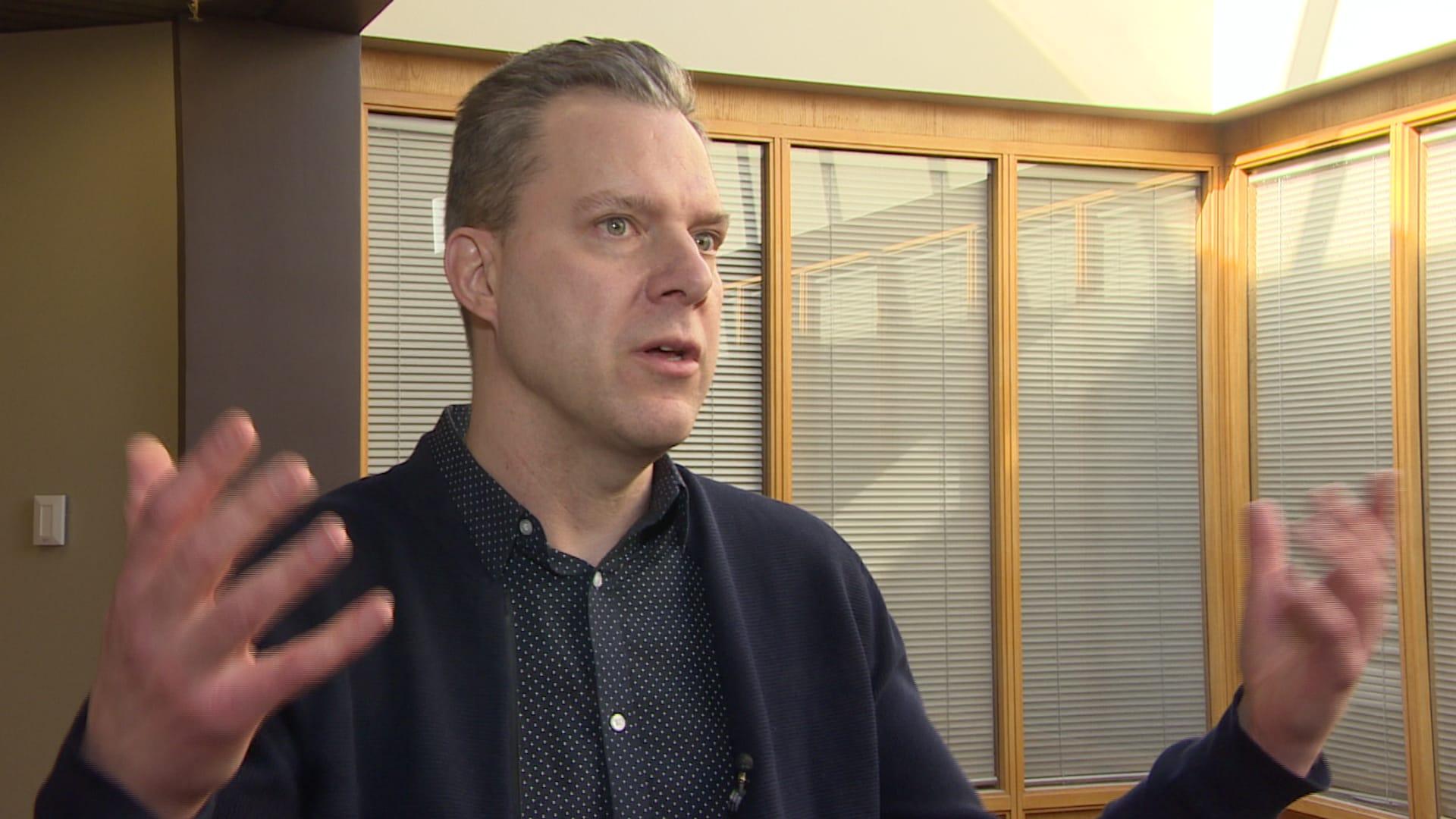 Un homme avec les bras en mouvement portant un veston bleu marine dans un couloir de l'Université de la Saskatchewan.