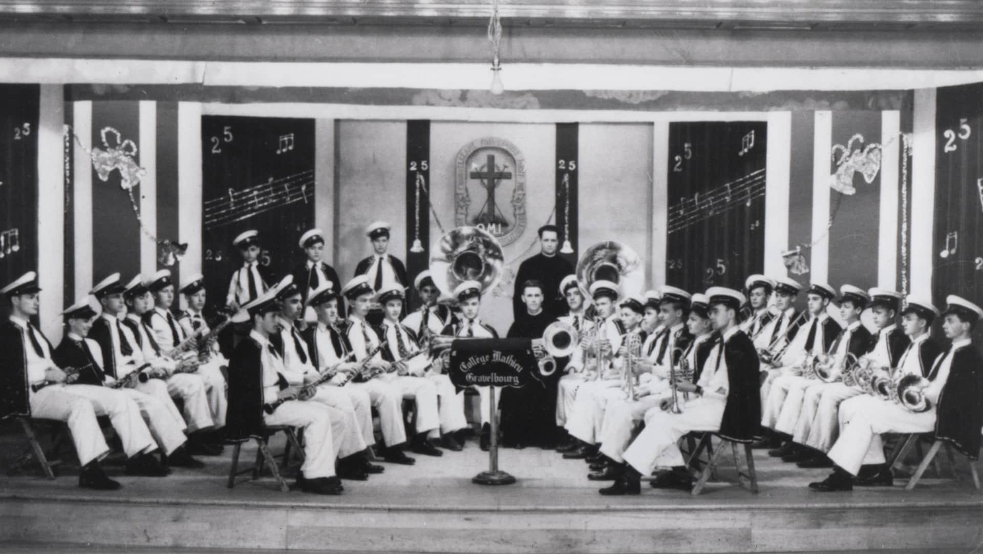 Des musiciens assis sur des chaises, en cercle, avec des instruments et des habits