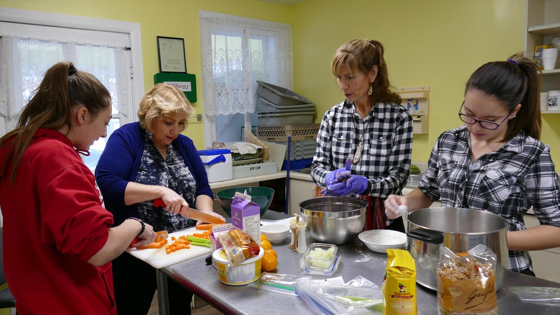 Deux femmes et deux filles coupent des légumes et forment des boulettes de viande sur un îlot de cuisine.