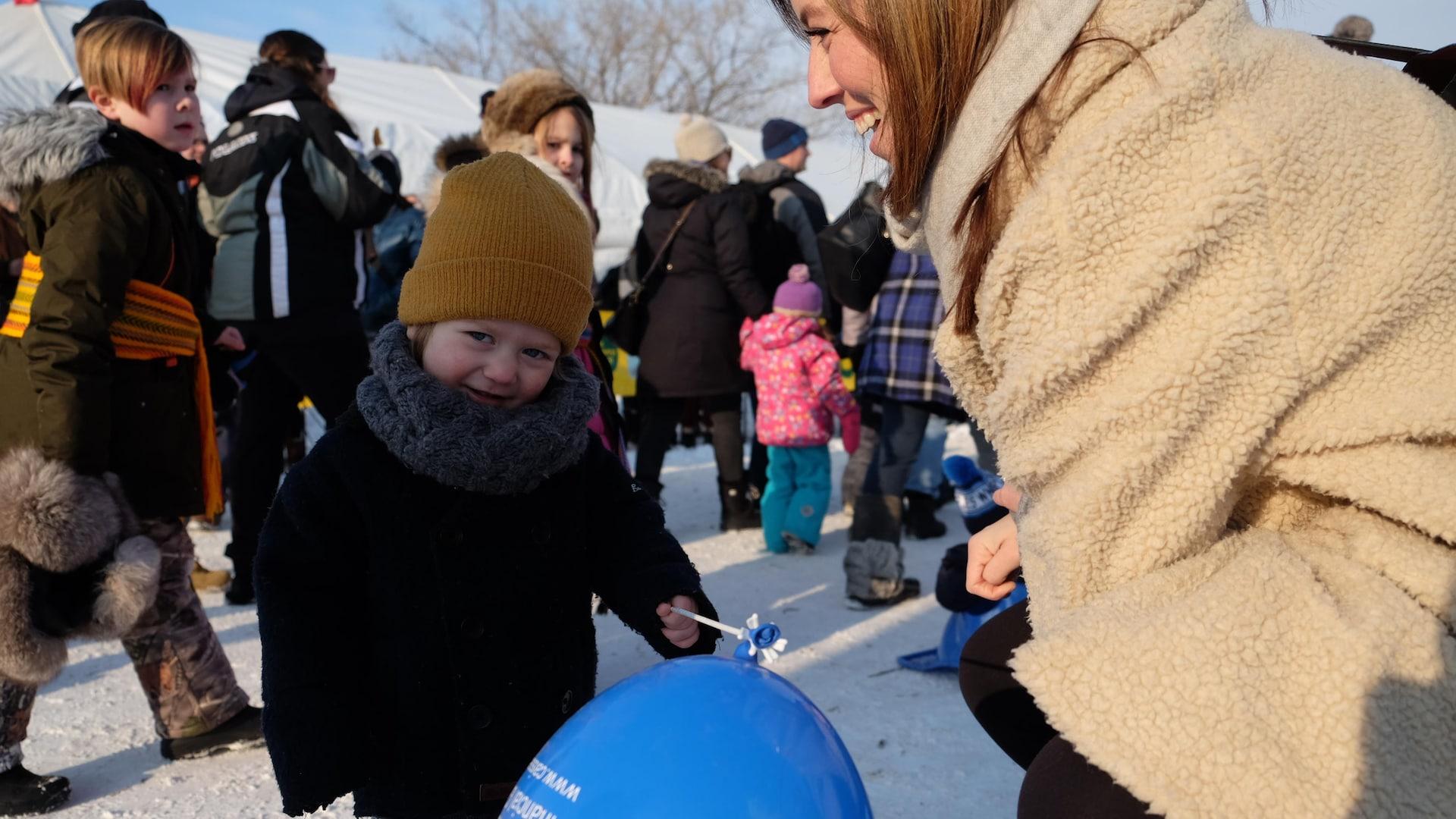 Un petit garçon tenant un ballon avec sa mère souriant à côté de lui.