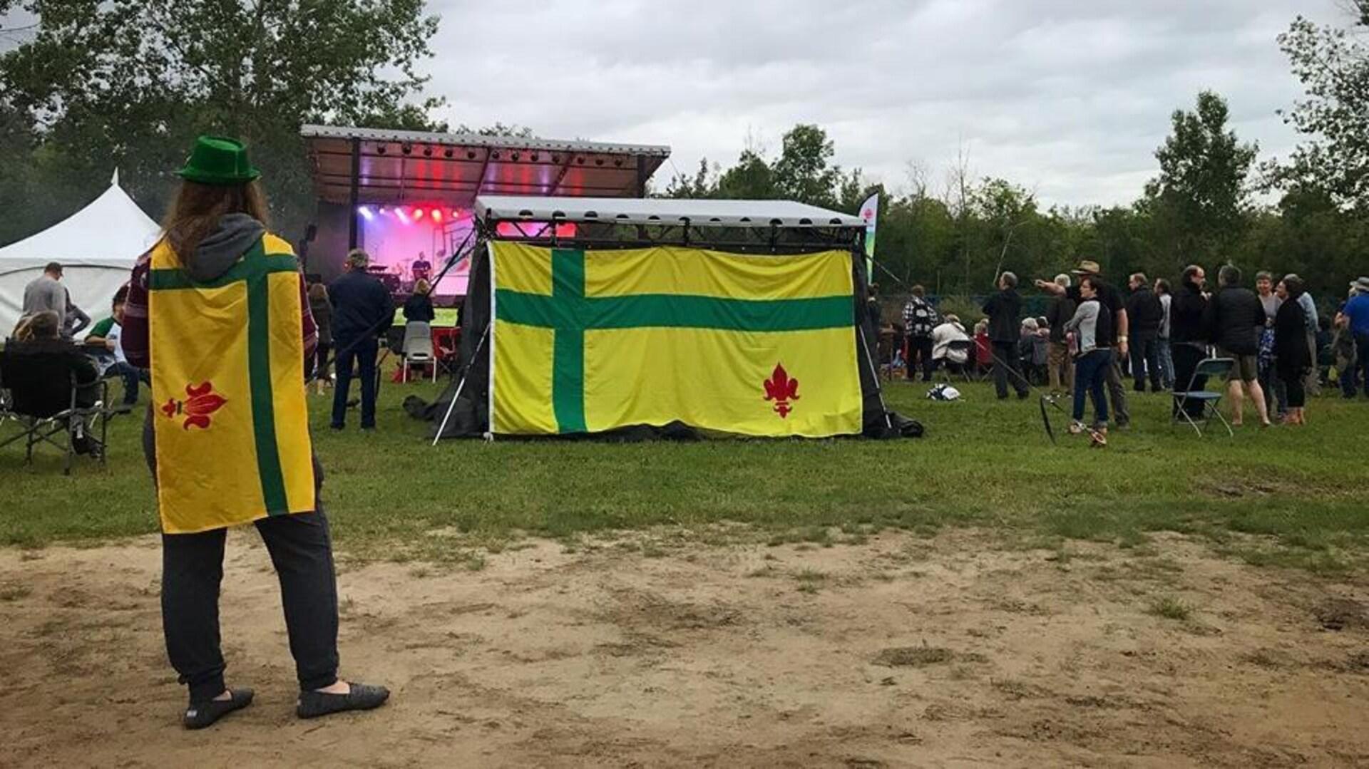 Festivalier arborant le drapeau fransaskois sur le site du festival.