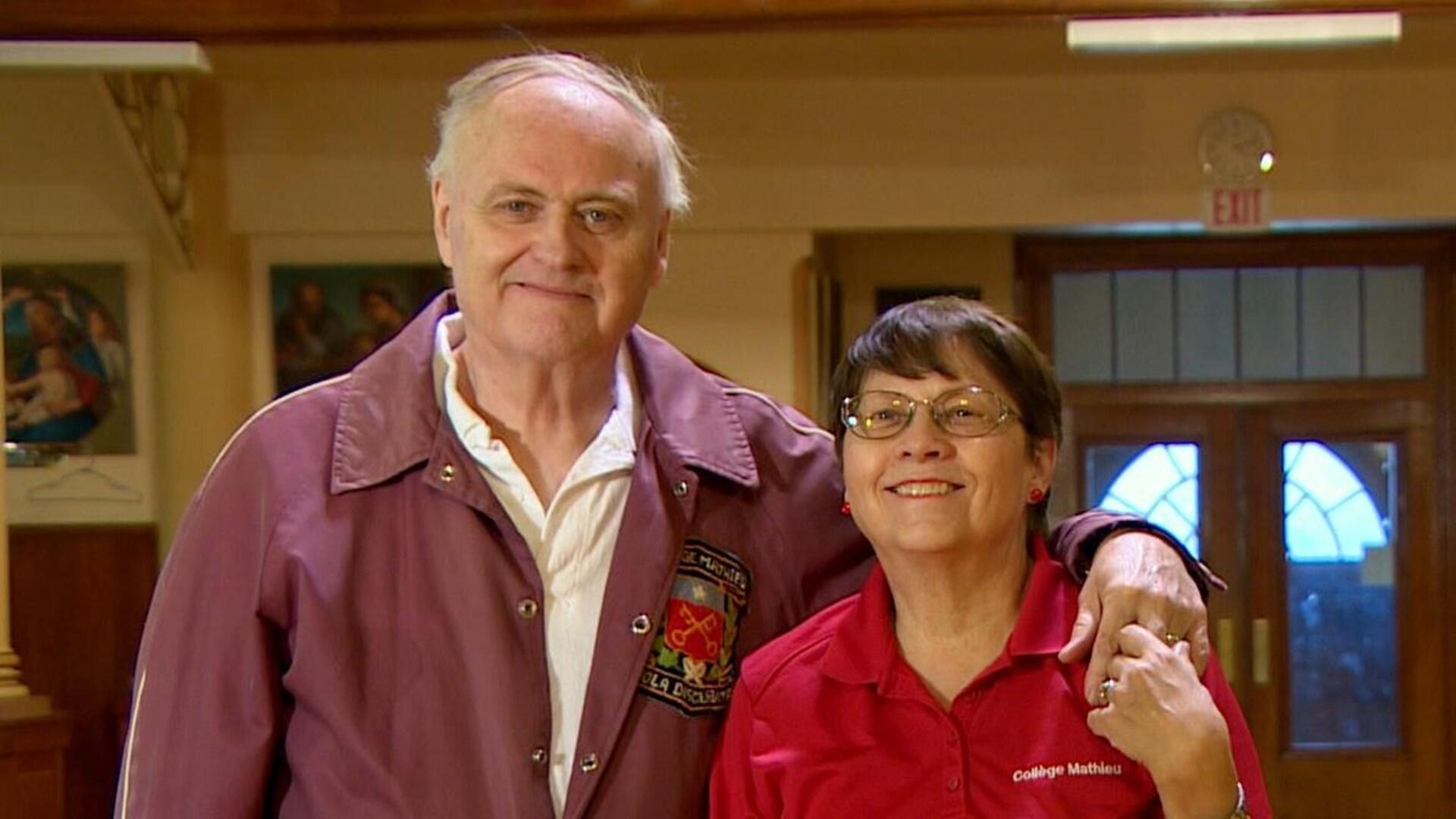 Un homme souriant tient une femme souriant par l'épaule, ils sont côte à côte. L'arrière-plan est un église.