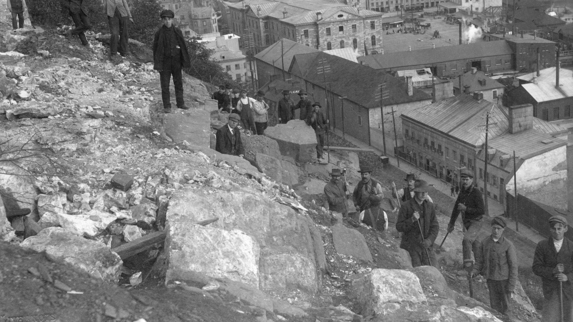 Des hommes et des adolescents triment dur à remblayer le haut de la falaise du Cap-Blanc, qui a été touché par plusieurs éboulements jusqu'en 1905, armés de pelles, ils prennent un instant de repos pour fixer le photographe. On voit l'ancien marché Champlain et une partie de la basse-ville en bas.