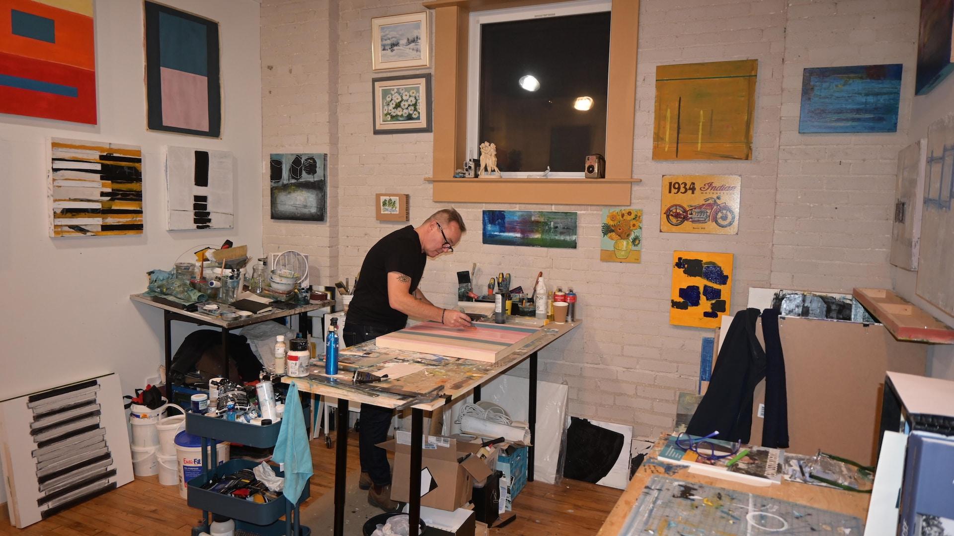 Jean-François Godbout au loin dans son studio, peint.