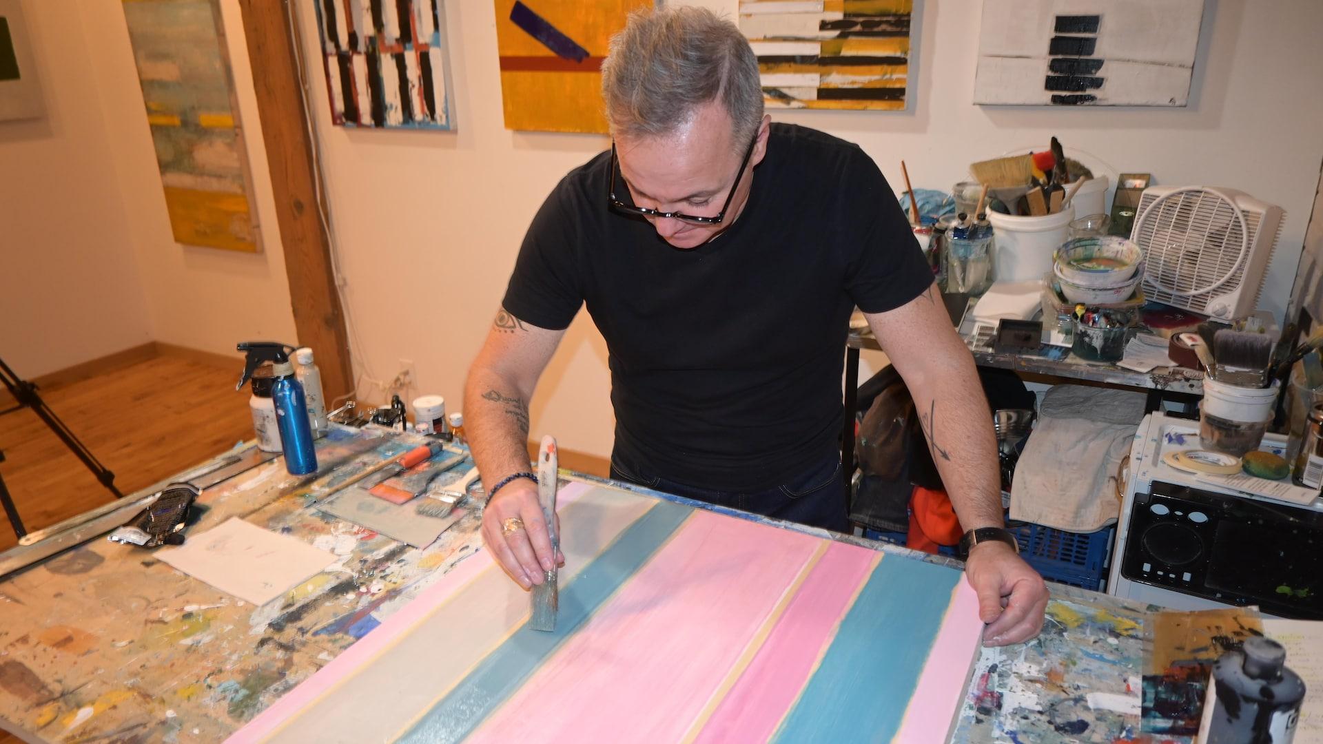 À l'aide d'un pinceau, l'artiste Jean-François Godbout applique de la peinture sur sa toile.