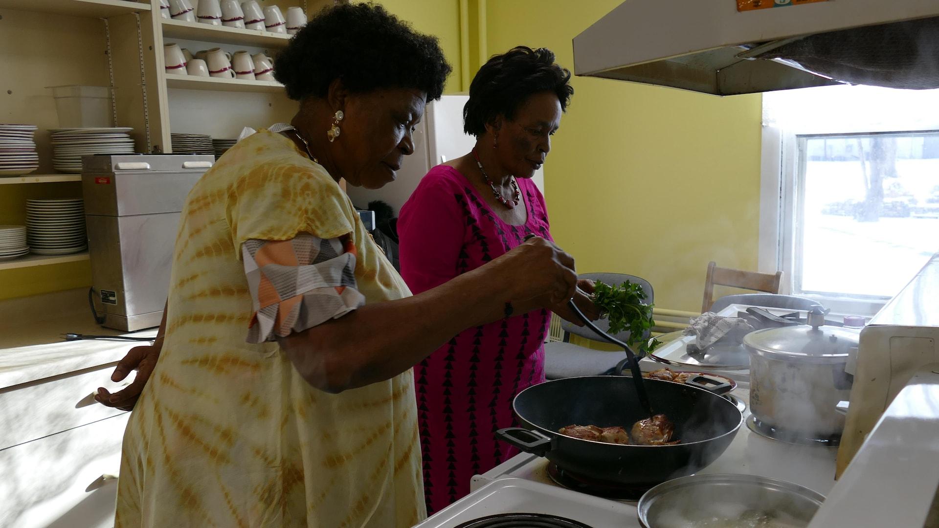 Deux grands-mères africaines cuisinent le poulet et le persil.