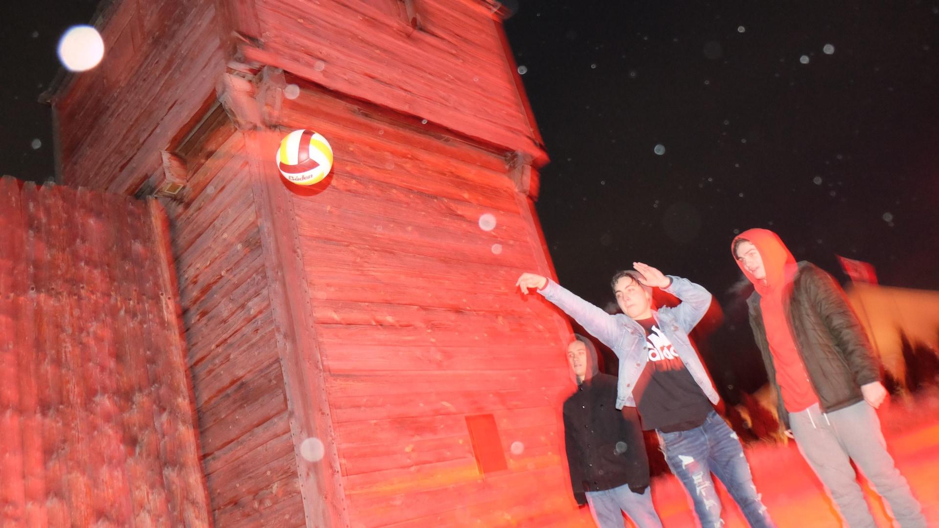 Des jeunes lancent un ballon dans la nuit, sous une légère neige.