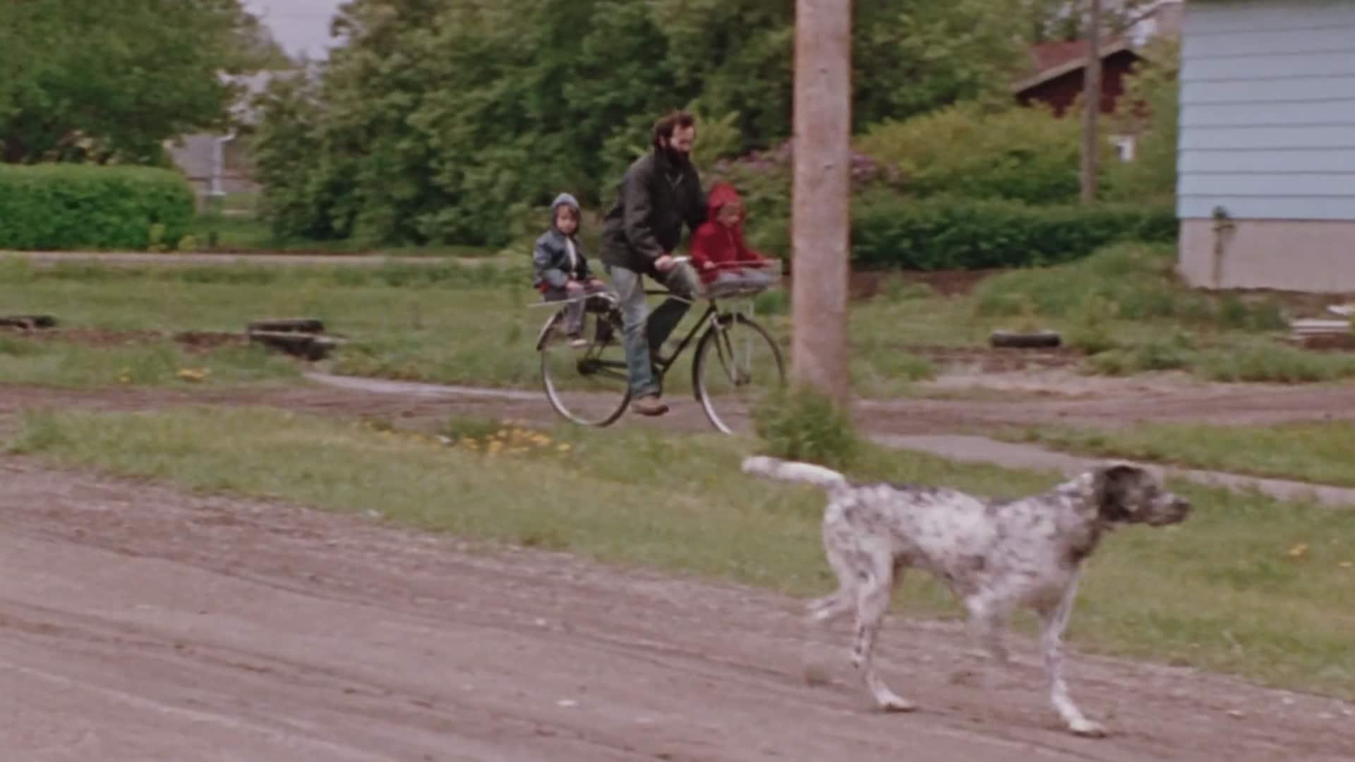 Joe Fafard sur son vélo avec deux enfants ainsi qu'un chien qui les suit.