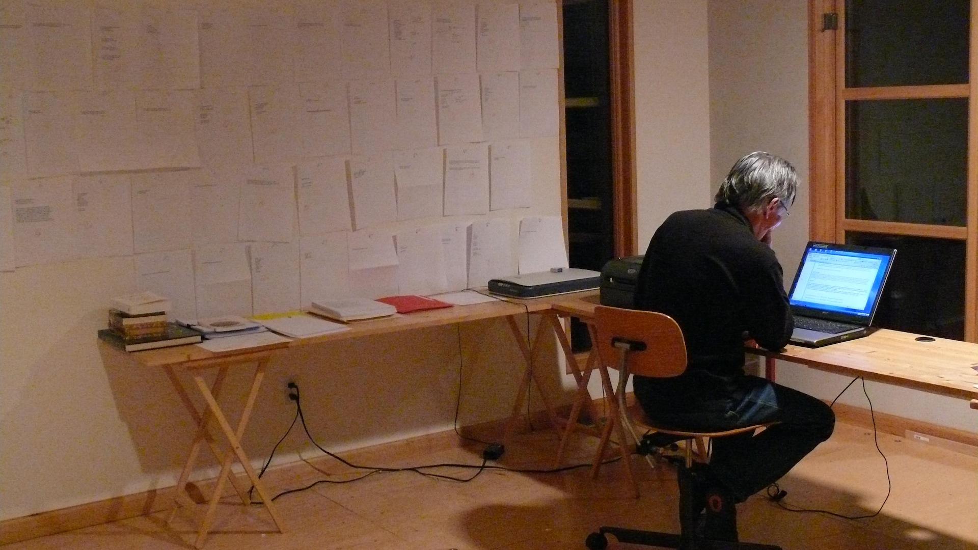 Une salle dépouillée, avec deux tables et un homme assis devant un ordinateur portable (de dos). Sur le mur, à sa gauche, des pages de manuscrit sont collées au mur.