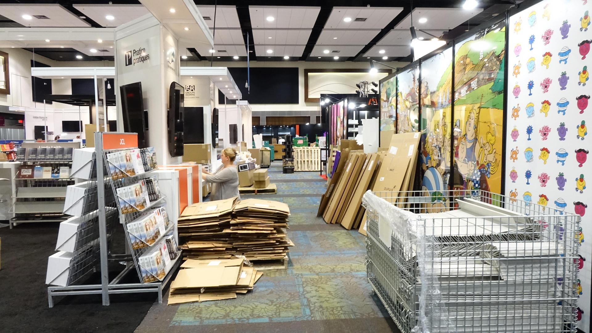 Des boîtes de cartons et des affiches entourent des kiosques en construction.
