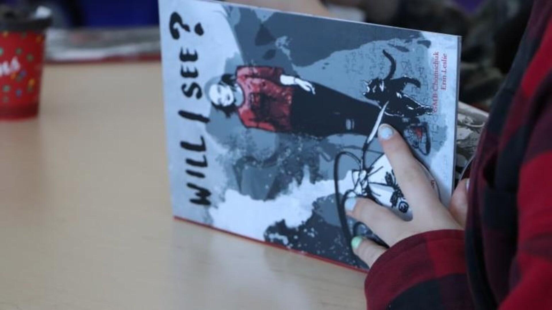 Une personne non identifiée consulte le roman graphique «Will I See?».