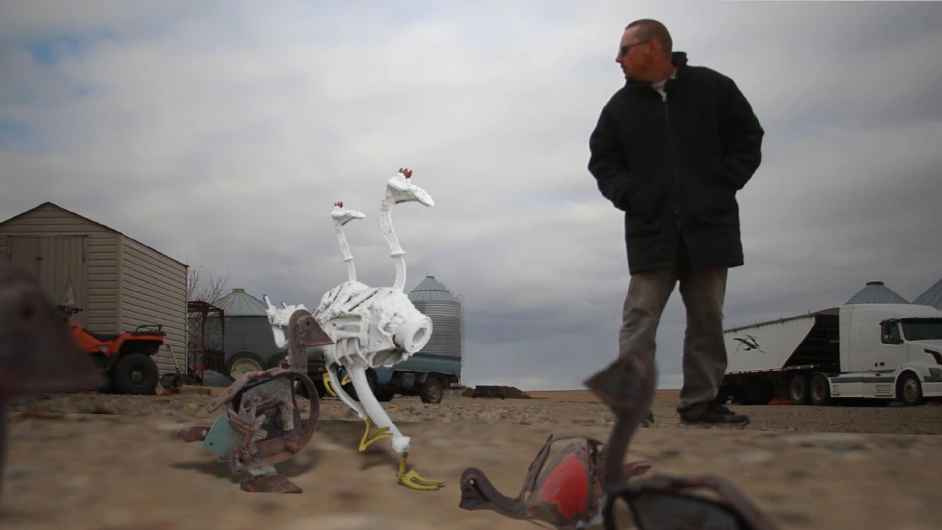 L'artiste fransaskois Lord Byrun fait semblant d'intéragir avec ses sculptures de poules en acier. Le ciel est menaçant.