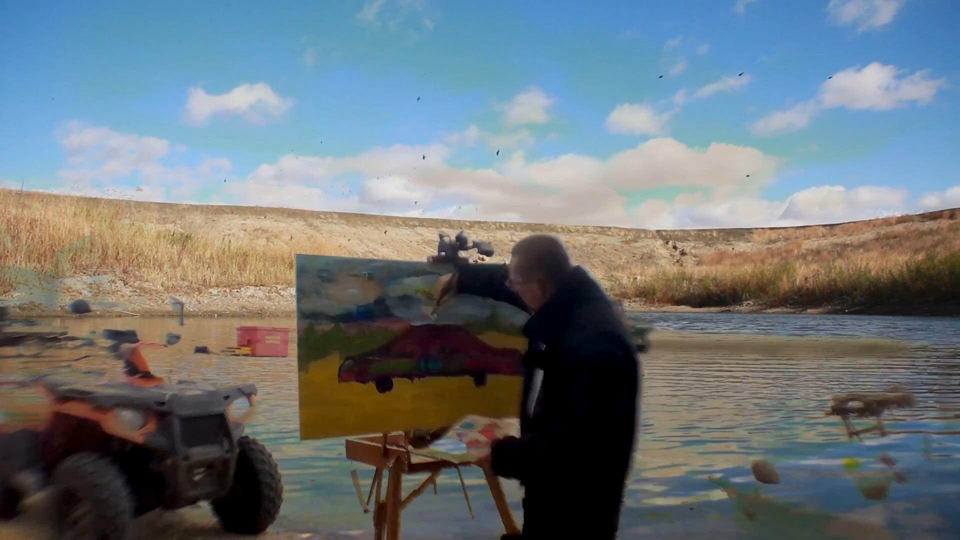 L'artiste fransaskois Lord Byrun crée un tableau d'une voiture multicolore. En arrière-plan se trouve un petit lac et un champ.