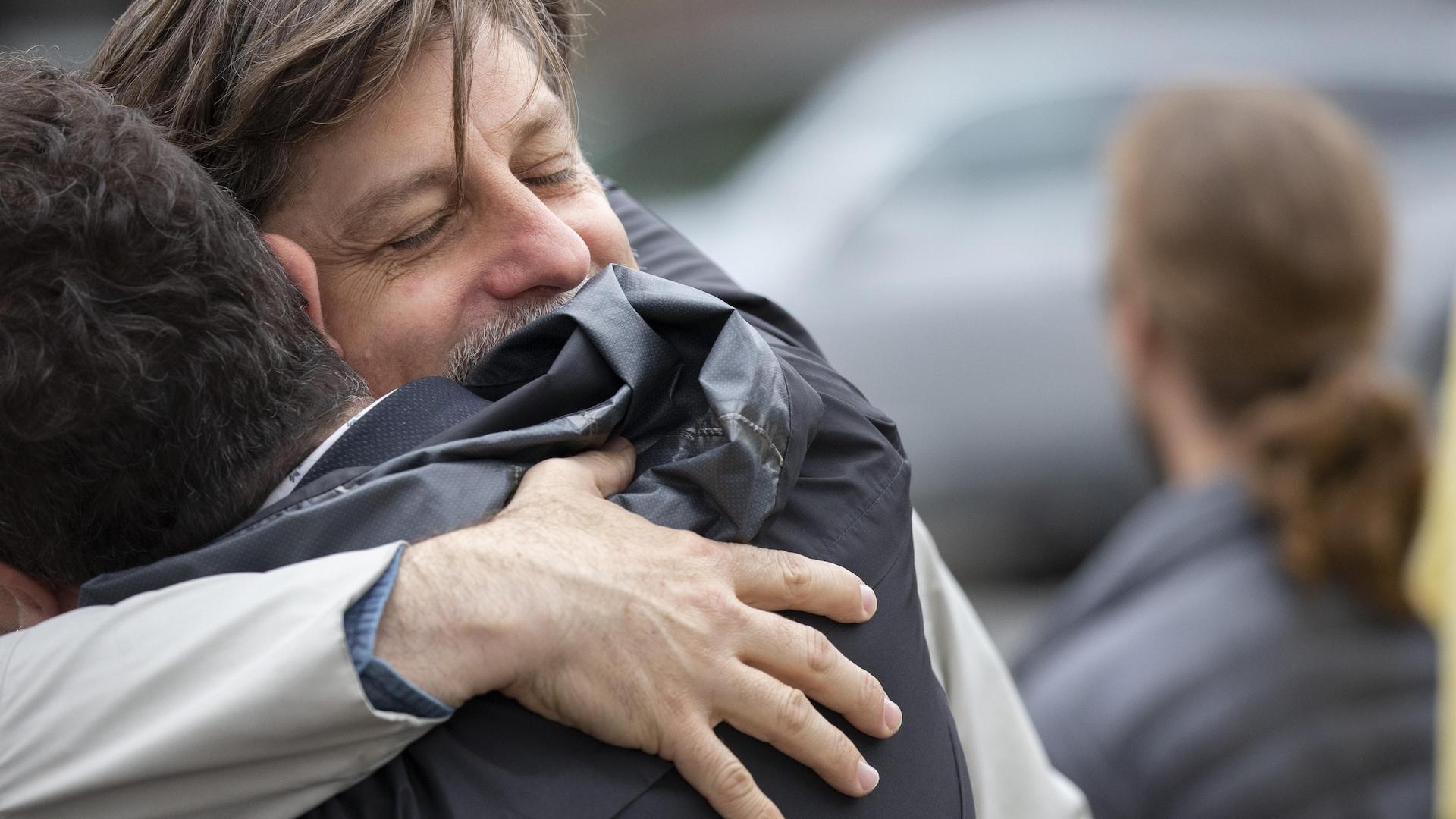 Un homme serre paternellement dans ses bras un adolescent.