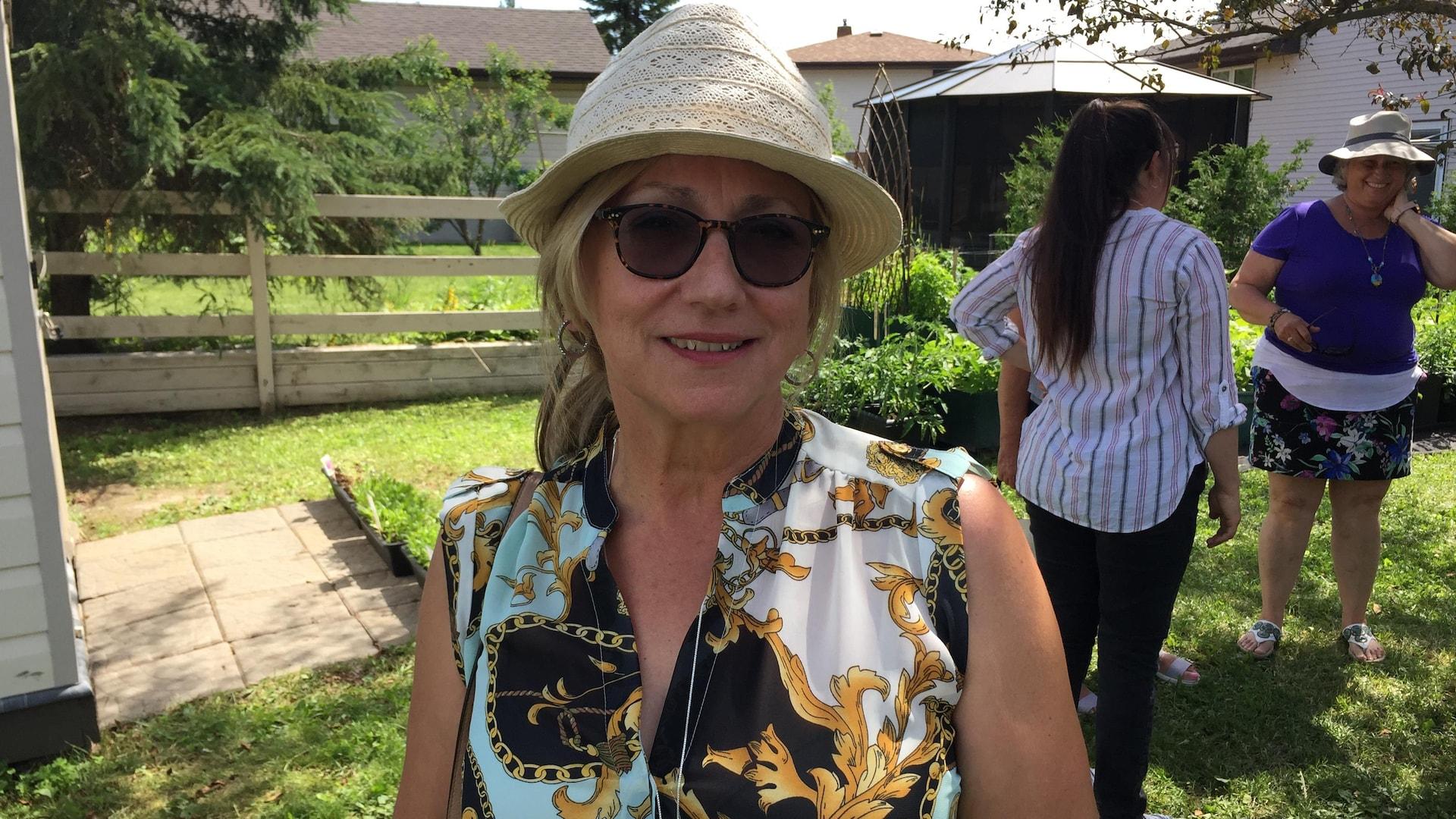 Une femme qui porte un chapeau et des lunettes de soleil