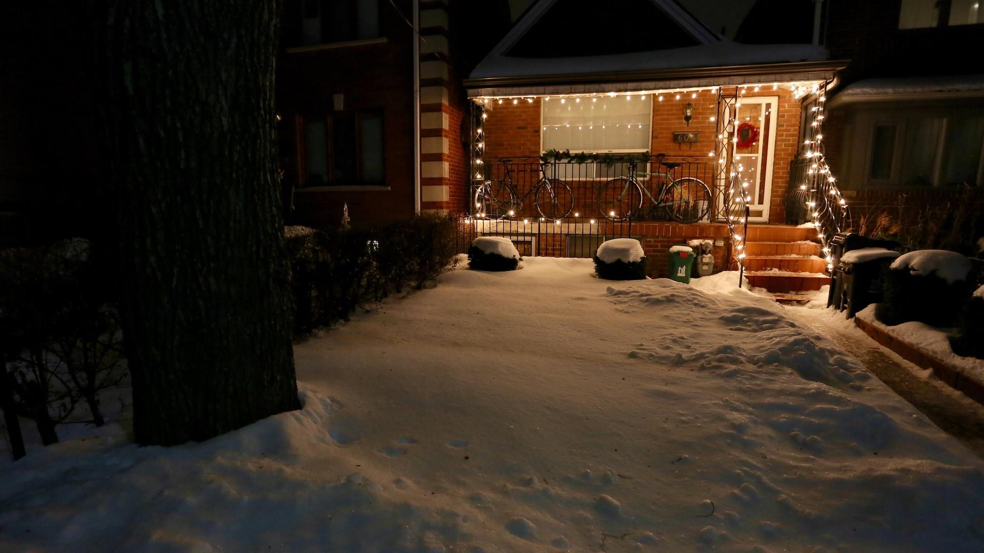 Photo de la maison avec sa cours enneigée.