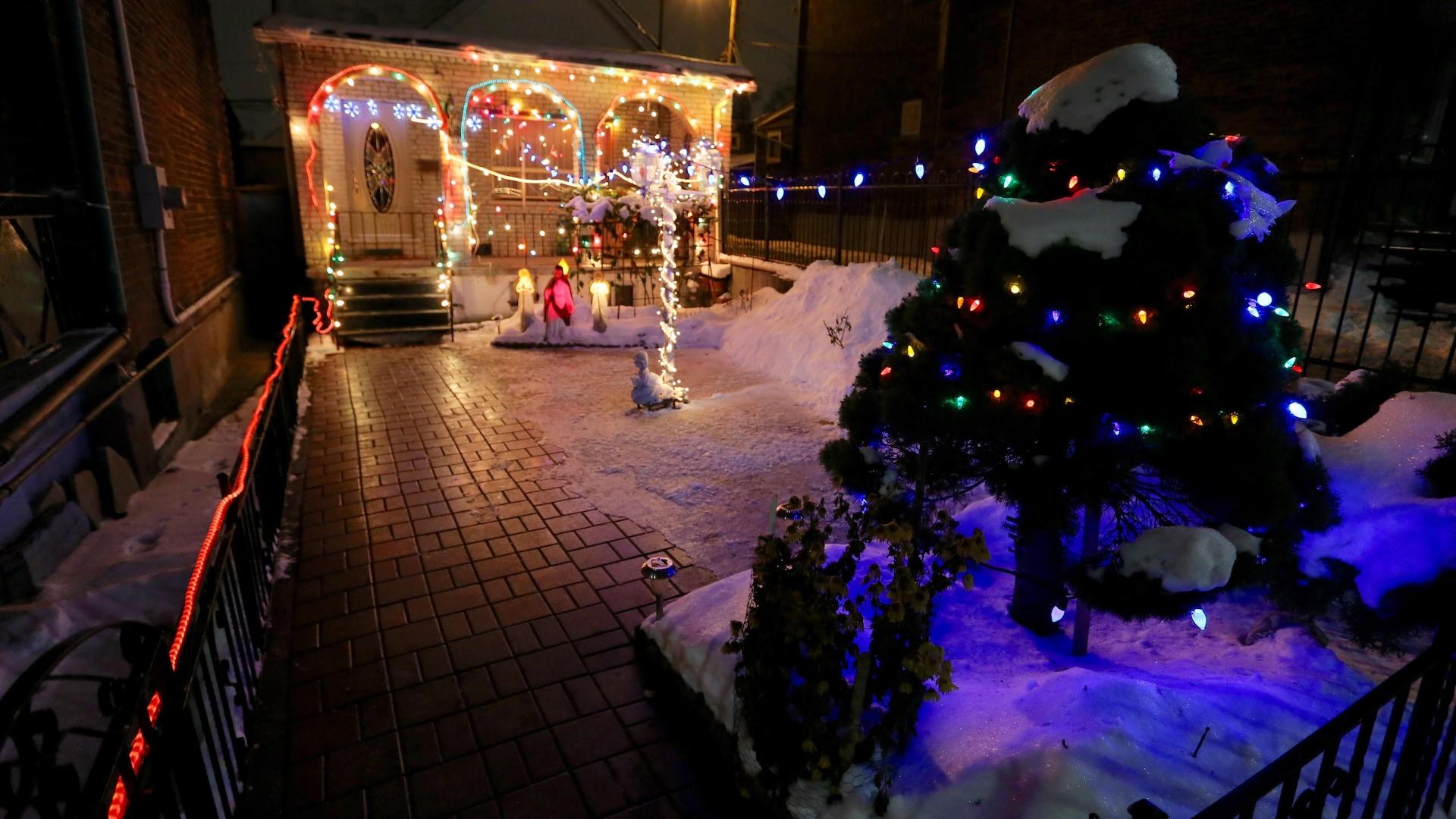 Photo de la maison avec sa cours illuminée de décorations.