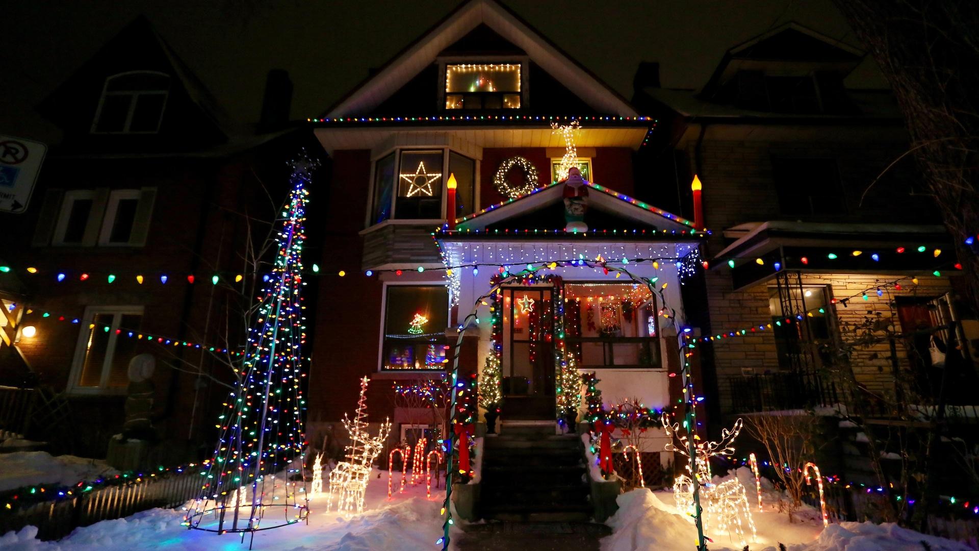 Photo de la maison avec un sapin, des rênes, d'énormes bougies, des guirlandes électriques et autres lumières.