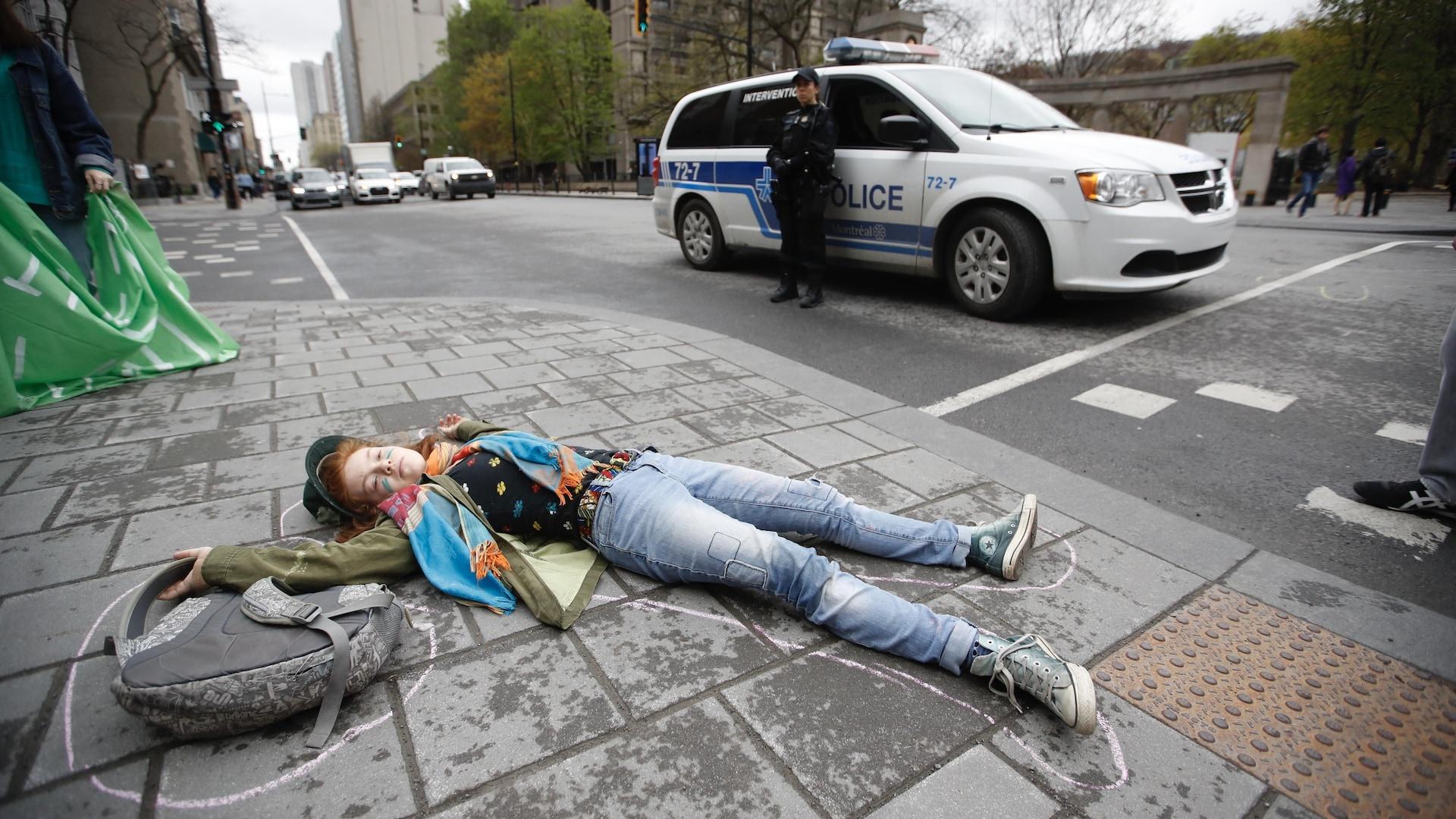 Une jeune fille est couchée par terre entourée d'un trait de craie, faisant la morte devant une camionnette de police.