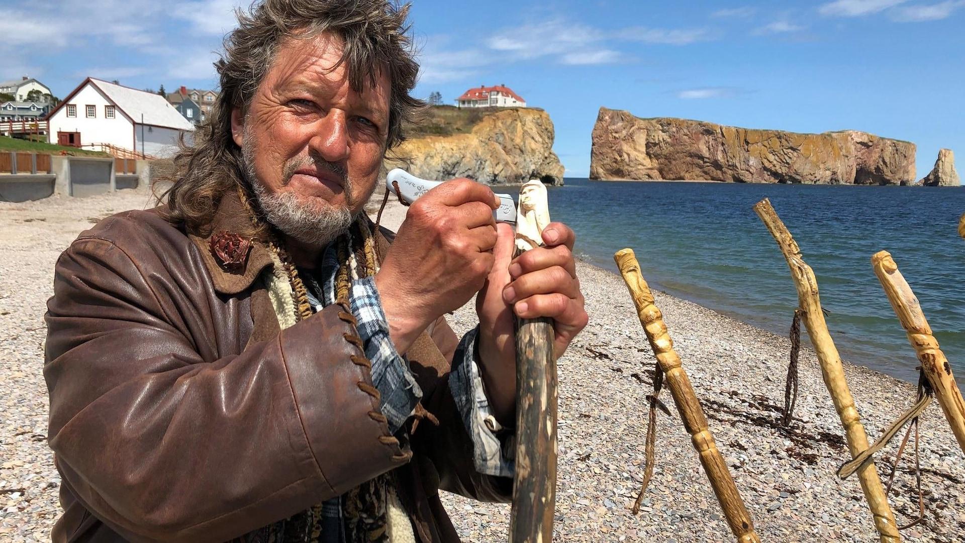 Un homme debout sur un plage avec derrière le rocher Percé