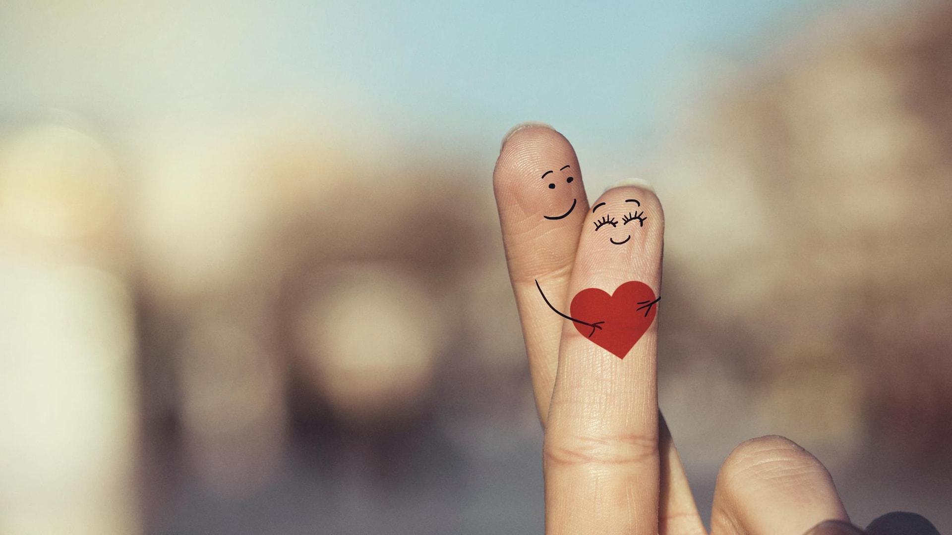 Photo d'un index et d'un majeur entrelacés sur lesquels des visages et un cœur ont été dessinés pour représenter des amoureux.