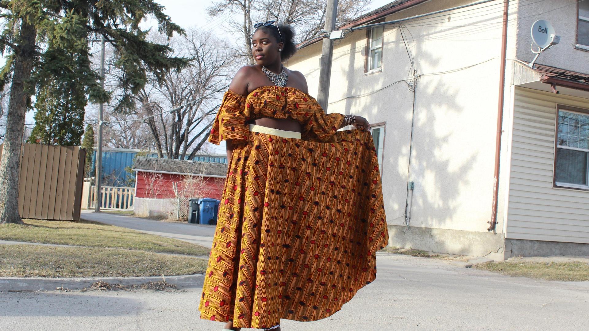 Une dame, dans la rue, pose avec sa robe en pagne.