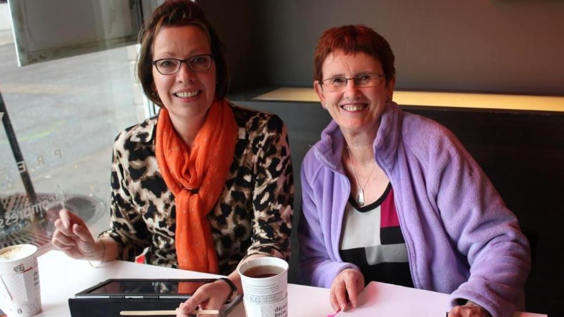 Deux femmes assises à une table avec cafés, tableau et dossier papier.