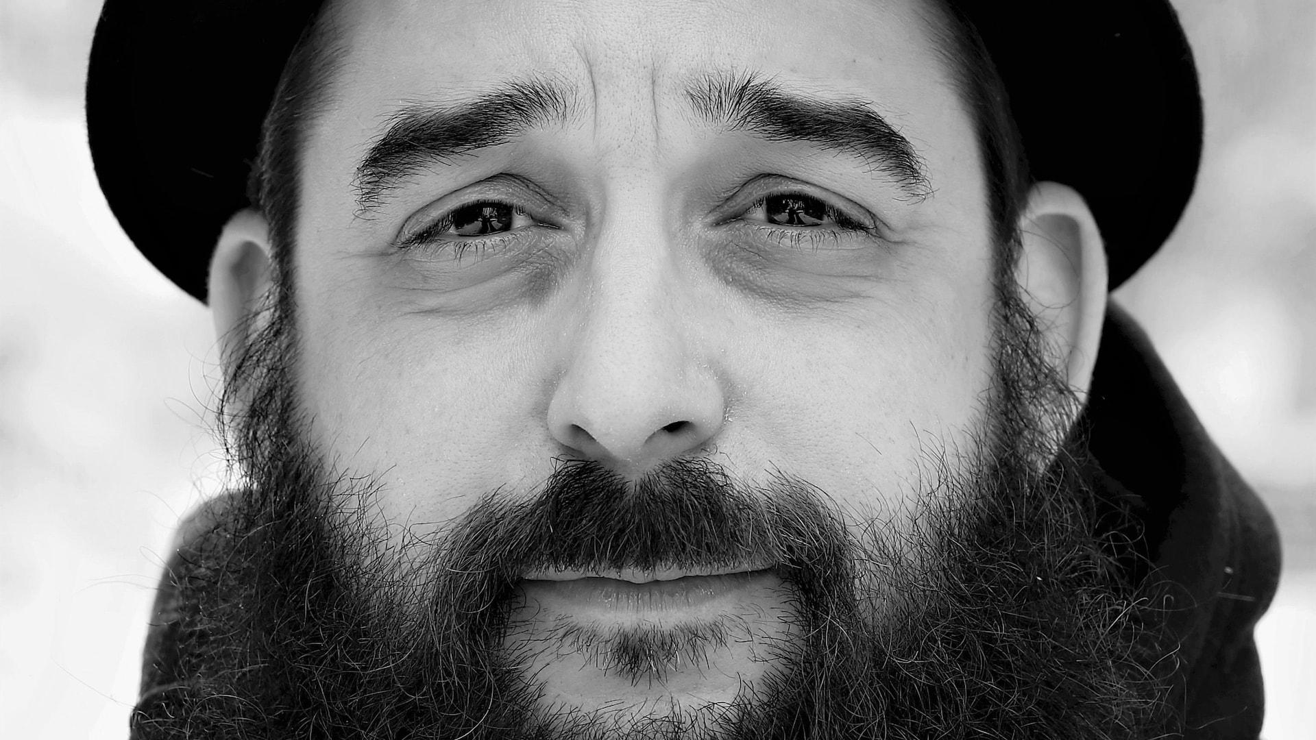 Portrait en noir et blanc, extérieur, de l'auteur Mathieu Blais. L'homme porte une barbe fournie et un chapeau. Il regarde la caméra, le front plissé.