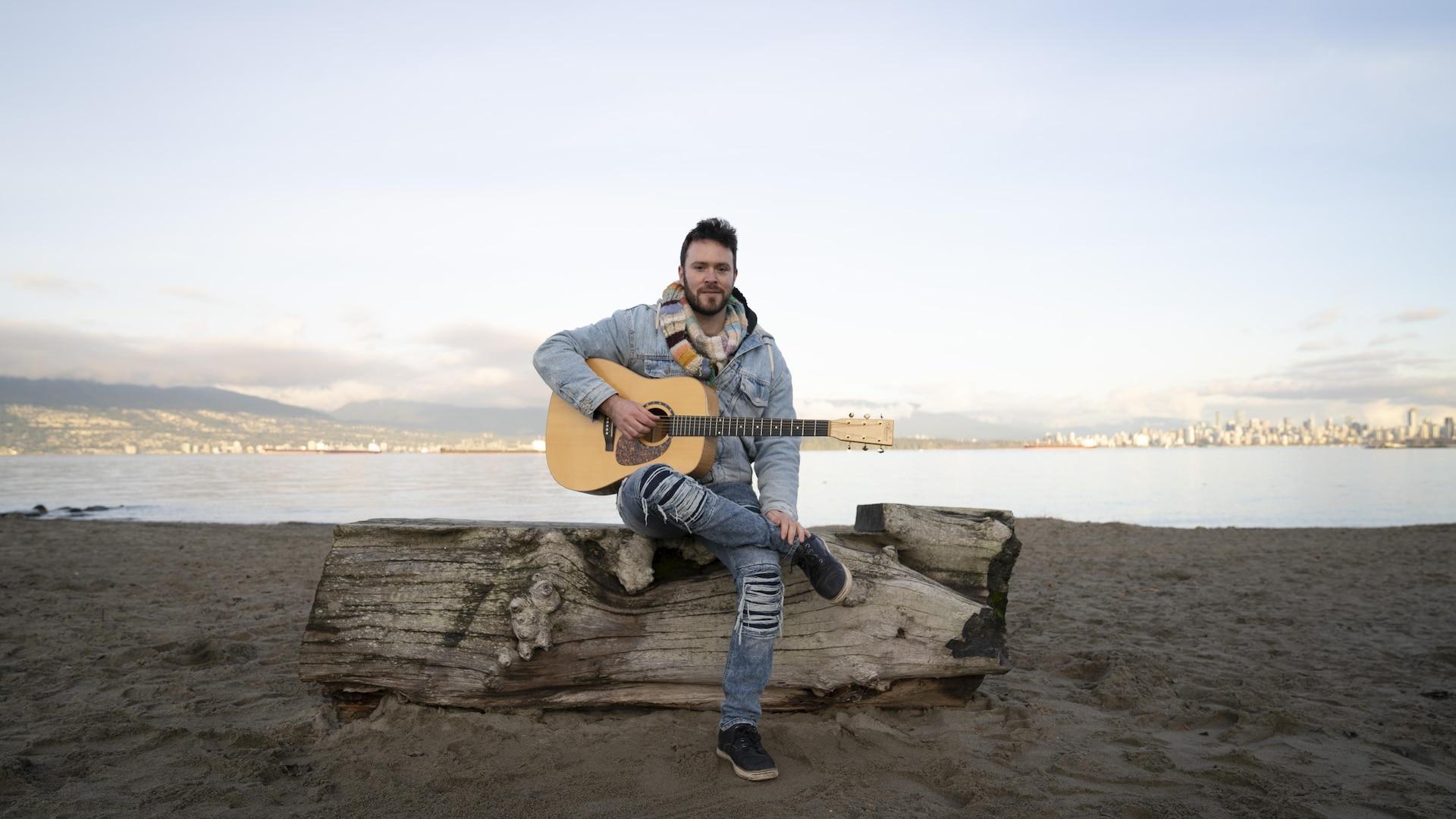 Matt Stern assis avec sa guitare sur un tronc d'arbre à la plage.