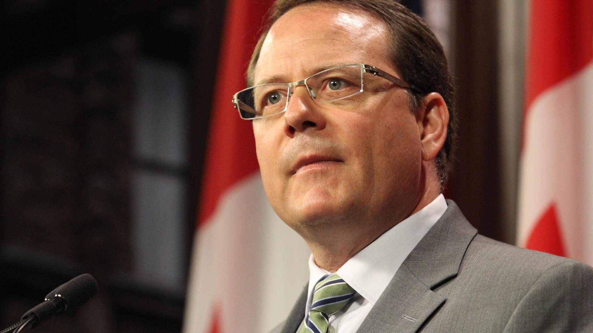 Un homme qui porte des lunettes devant des drapeaux canadiens