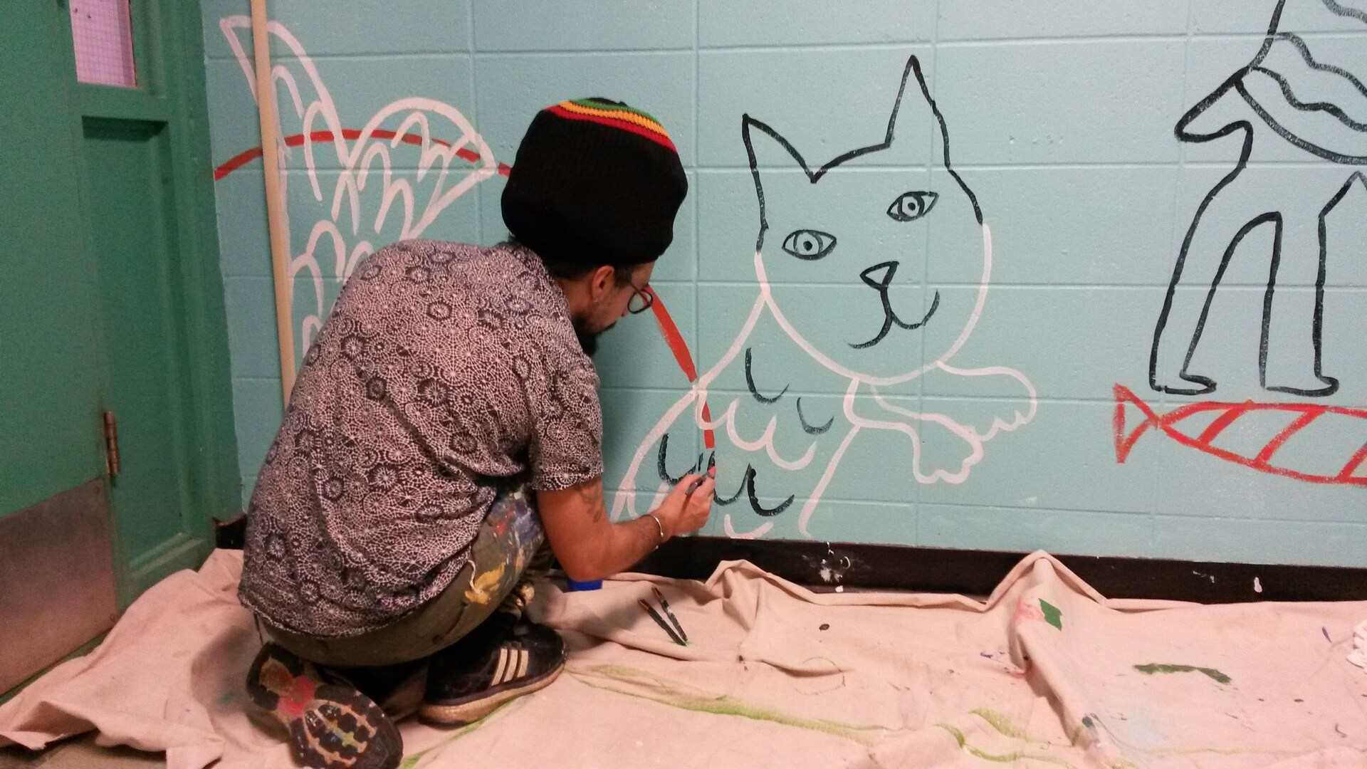 L'artiste Julian Palma, de l'organisme MU trace un dessin au pinceau sur le mur d'une école pendant un atelier de création de murale en milieu scolaire.