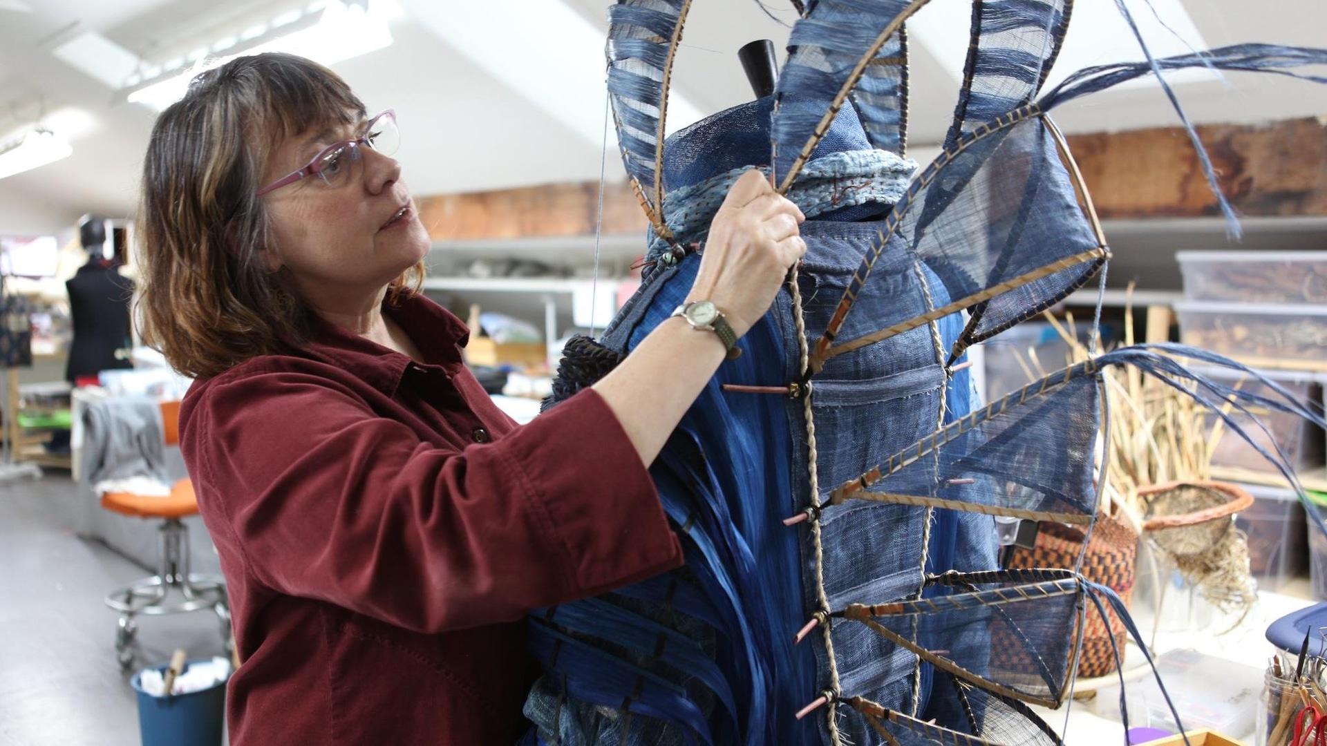 Nicole Dextras ajuste un élément d'un costume de son projet Chronos fait de matières naturelles.