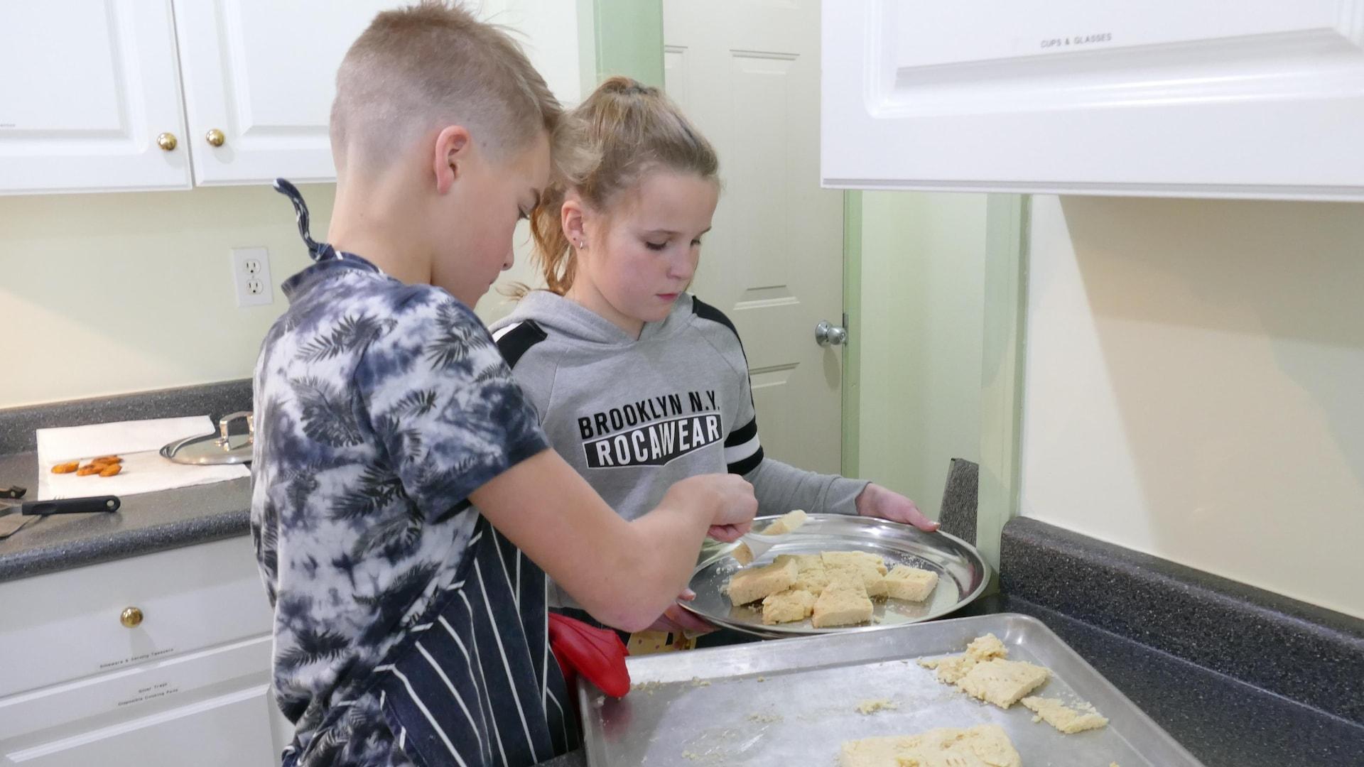 Noah et Abby découpent la galette métisse et placent les morceaux sur un plat de service.
