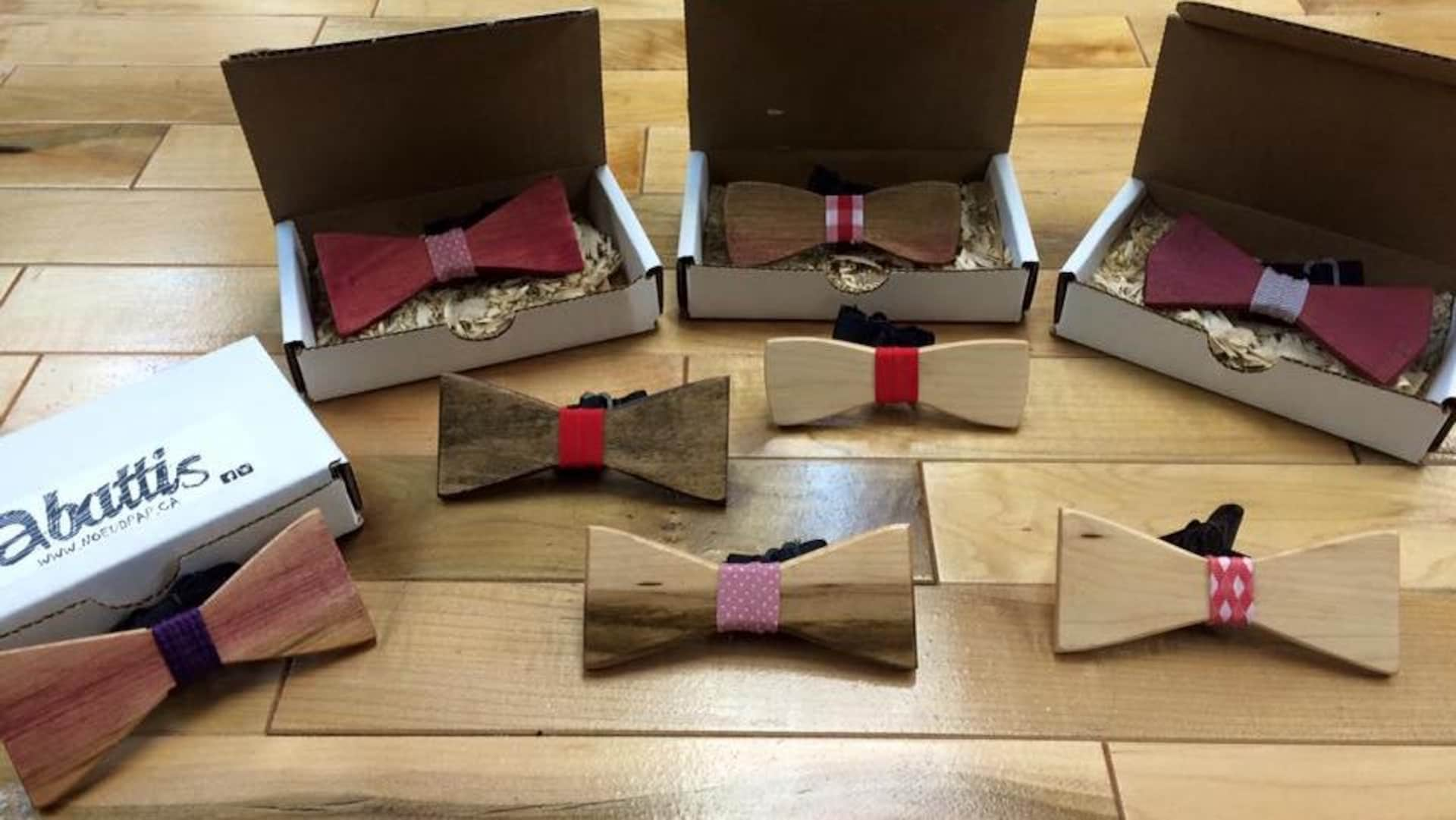 Huit exemples de noeuds papillon de la compagnie Abattis Noeud Pap de Saguenay sont étalés sur le plancher.