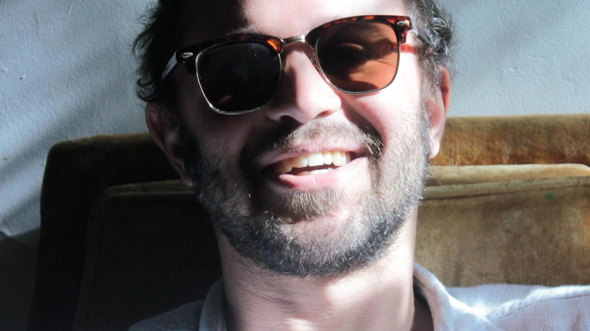 Portrait en couleur d'Olyvier Leroux-Picard, souriant, avec des lunettes de soleil.