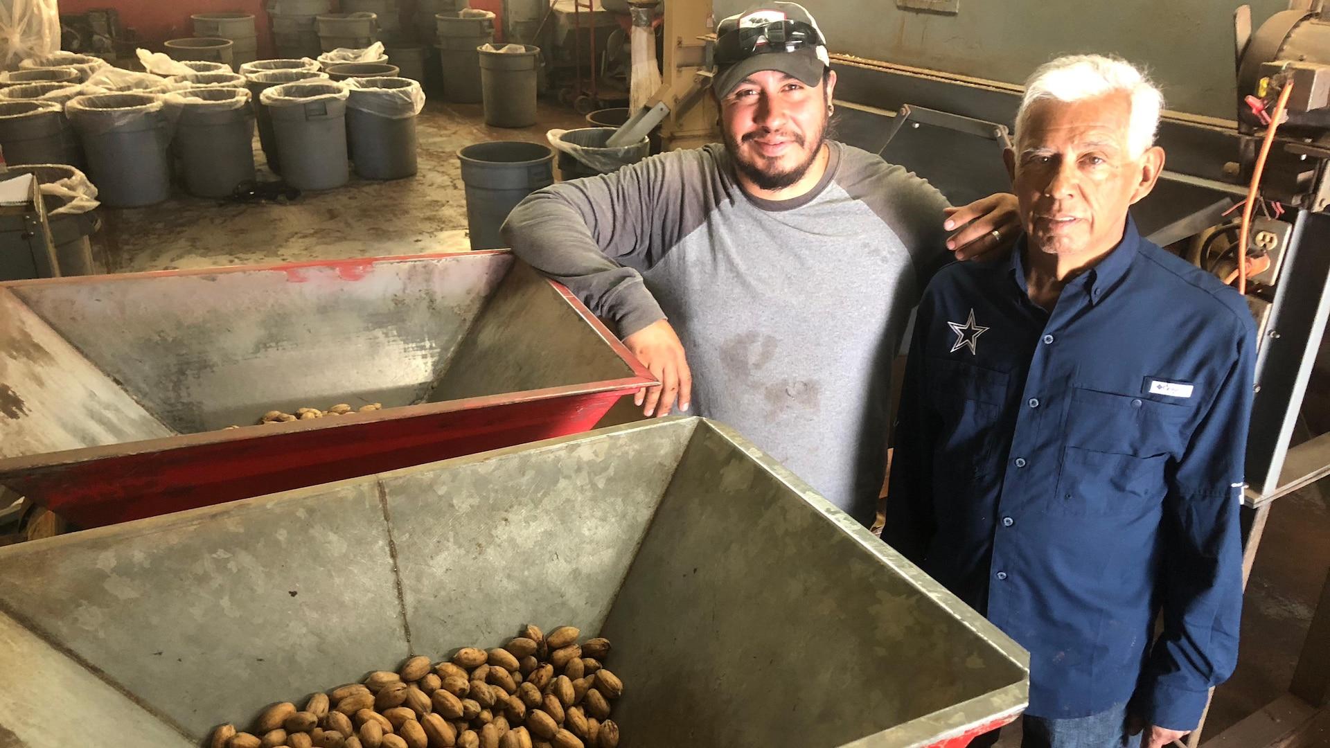 Un jeune homme portant une casquette et son père sourient devant une machine contenant des pacanes.