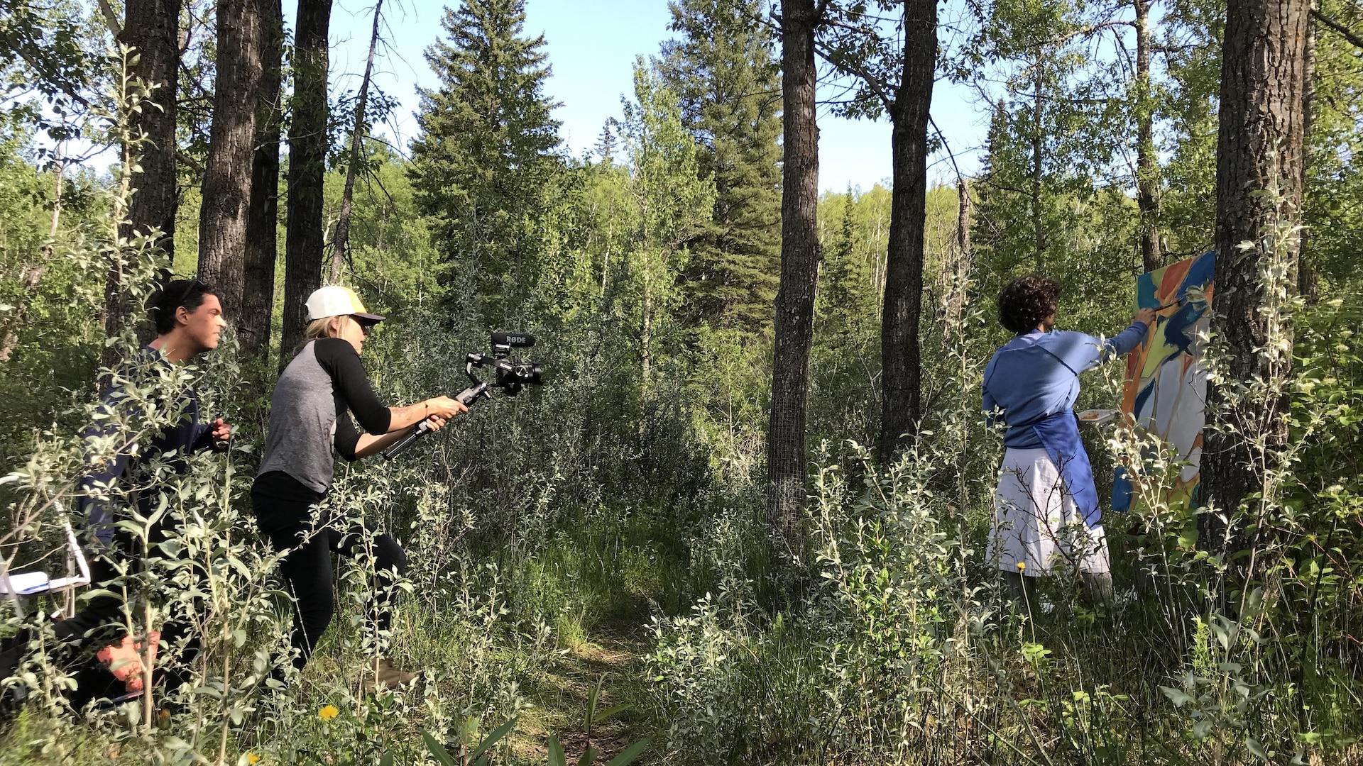 Deux personnes filment Patricia Lortie dans une forêt en train de peindre une toile déposée sur un chevalet.
