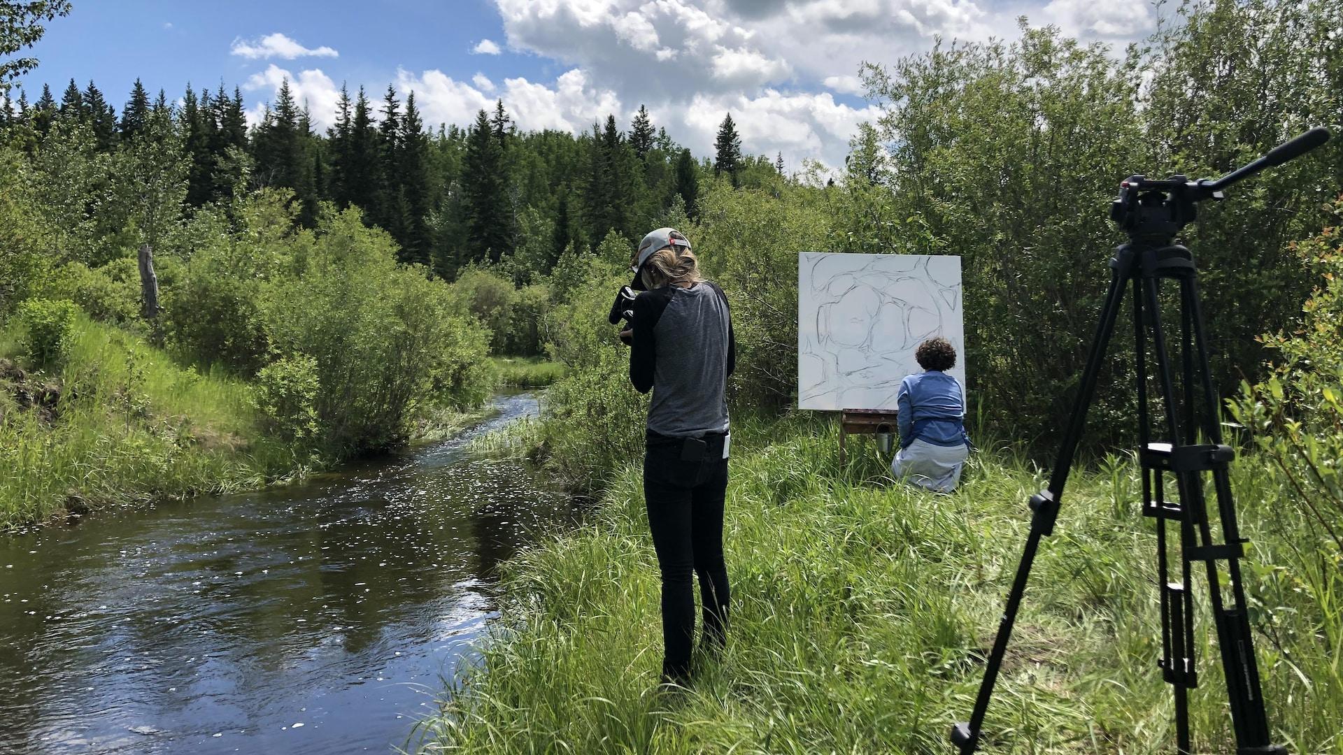 Une femme filme Patricia Lortie dans une forêt en train de peindre une toile déposée sur un chevalet, près d'une rivière.