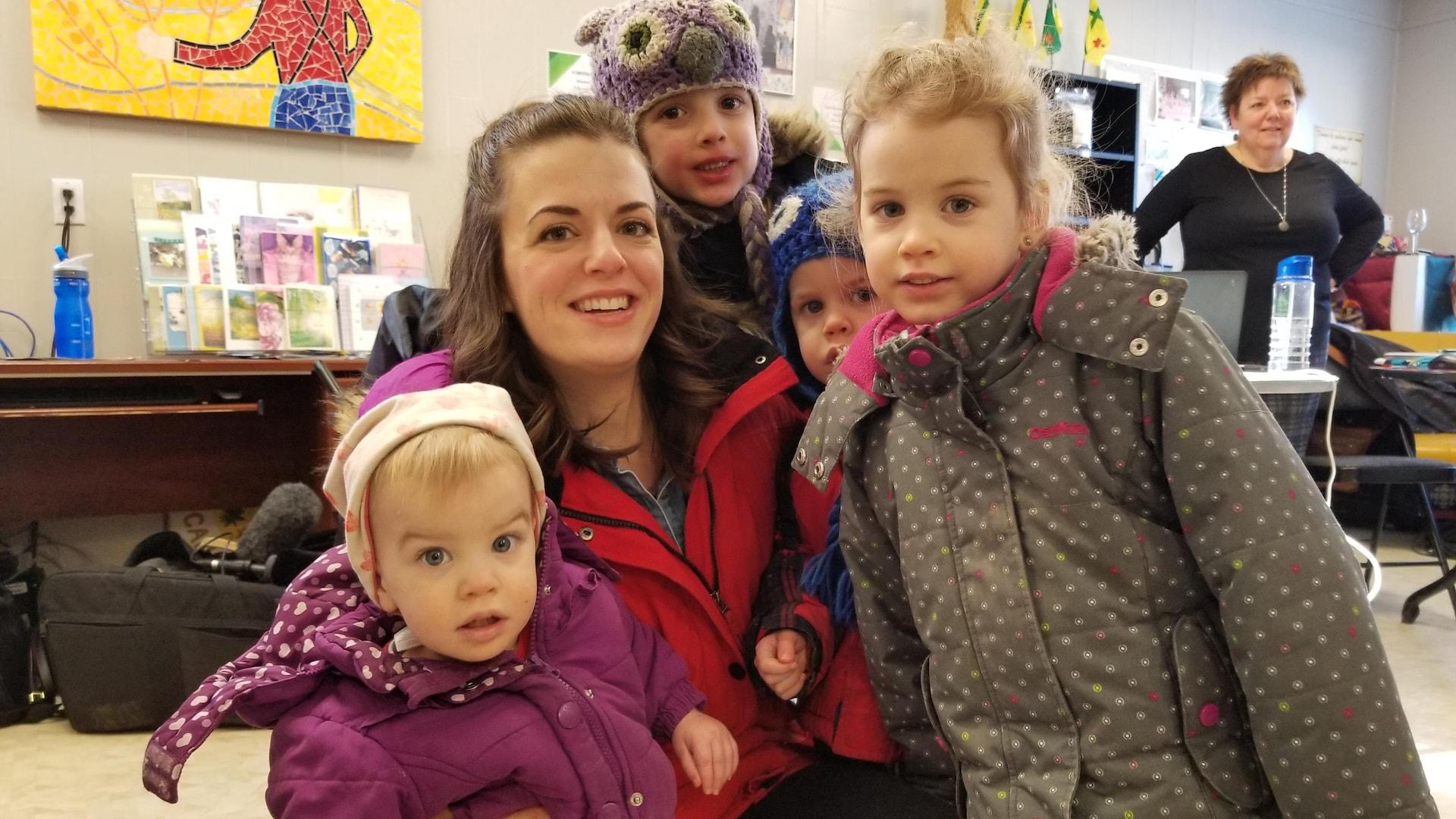 Une famille avec la maman au centre ainsi que quatre enfants autour d'elle.