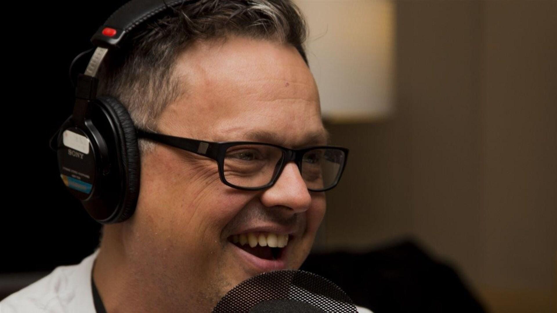 Photographié de profil, l'écrivain Éric Dupont rit alors qu'il se trouve devant un micro de studio radio.